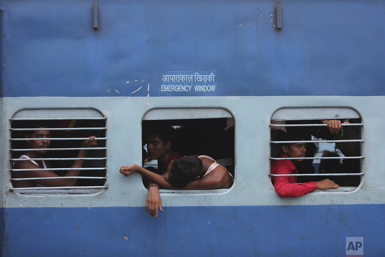 Indian migrant laborers sit inside a train as they prepare to leave the region, at a railway station in Jammu, India, Wednesday, Aug. 7, 2019. (AP Photo/Channi Anand)