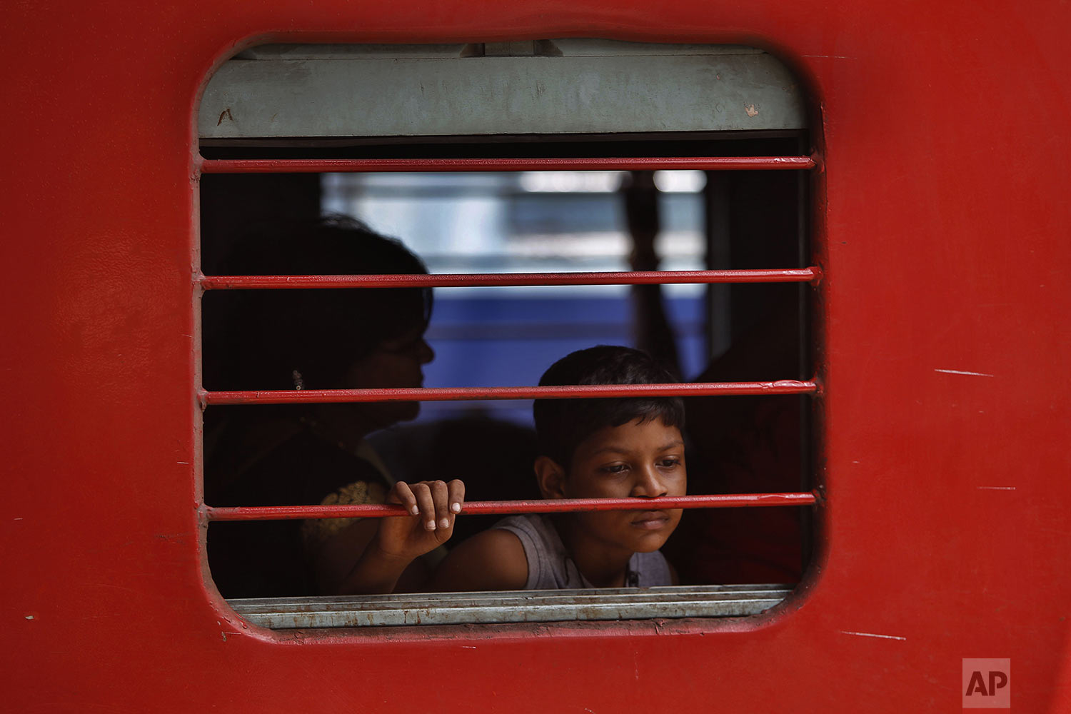 An Indian boy sits inside a train waiting to leave a railway station in Jammu, India, Sunday, Aug. 4, 2019. (AP Photo/Channi Anand)
