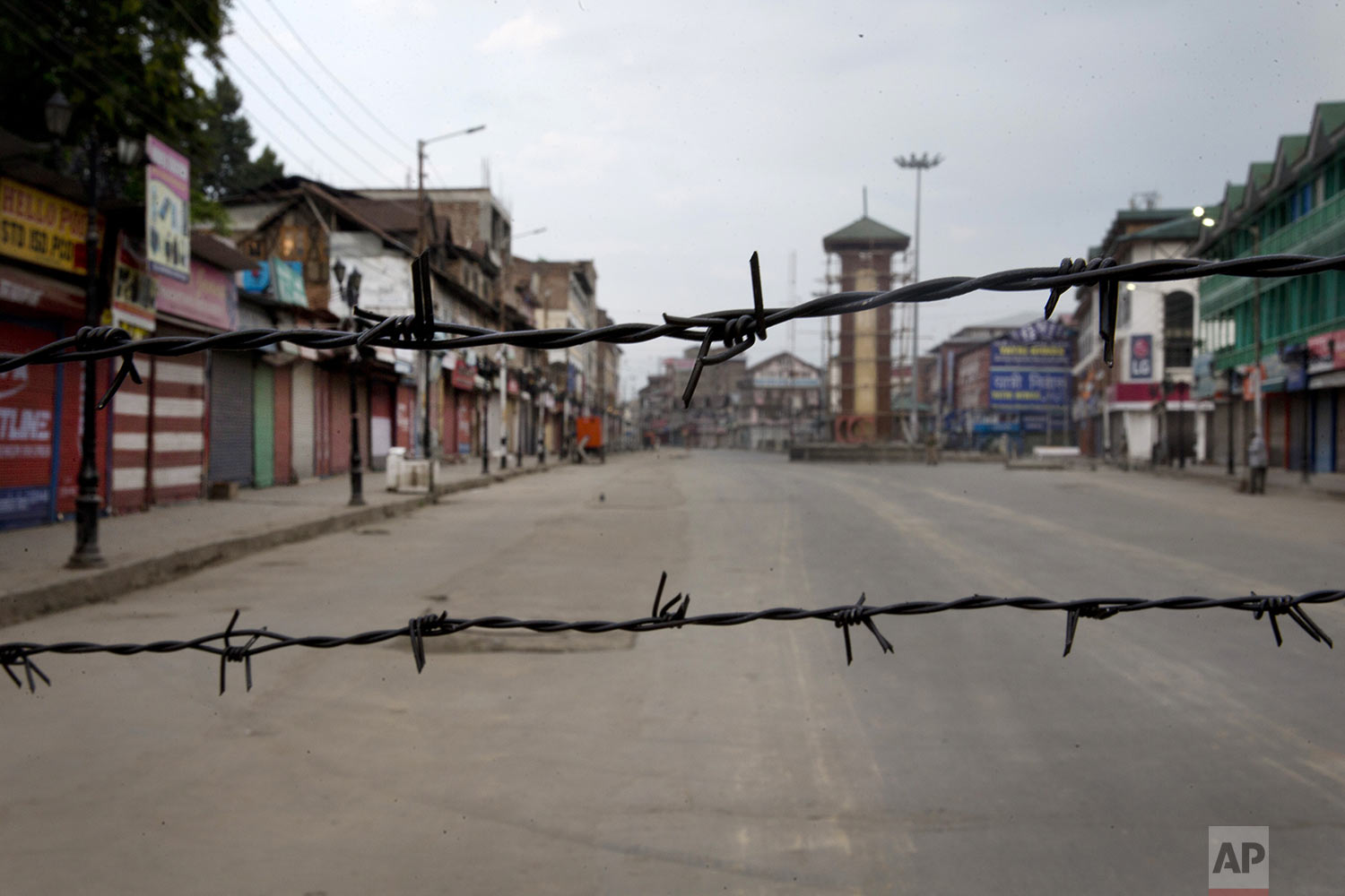 A deserted street is seen through a barbwire set up as blockade during curfew in Srinagar, Indian controlled Kashmir, Tuesday, Aug. 6, 2019. (AP Photo/Dar Yasin)
