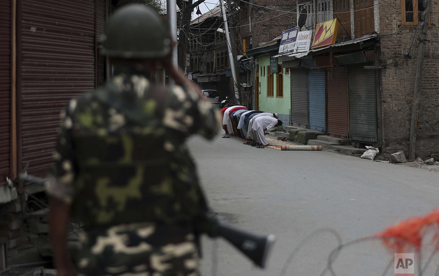 An Indian paramilitary soldier stands guard as Kashmiri Muslims offer Friday prayers on a street outside a local mosque during curfew like restrictions in Srinagar, India, Friday, Aug. 16, 2019. (AP Photo/Mukhtar Khan)
