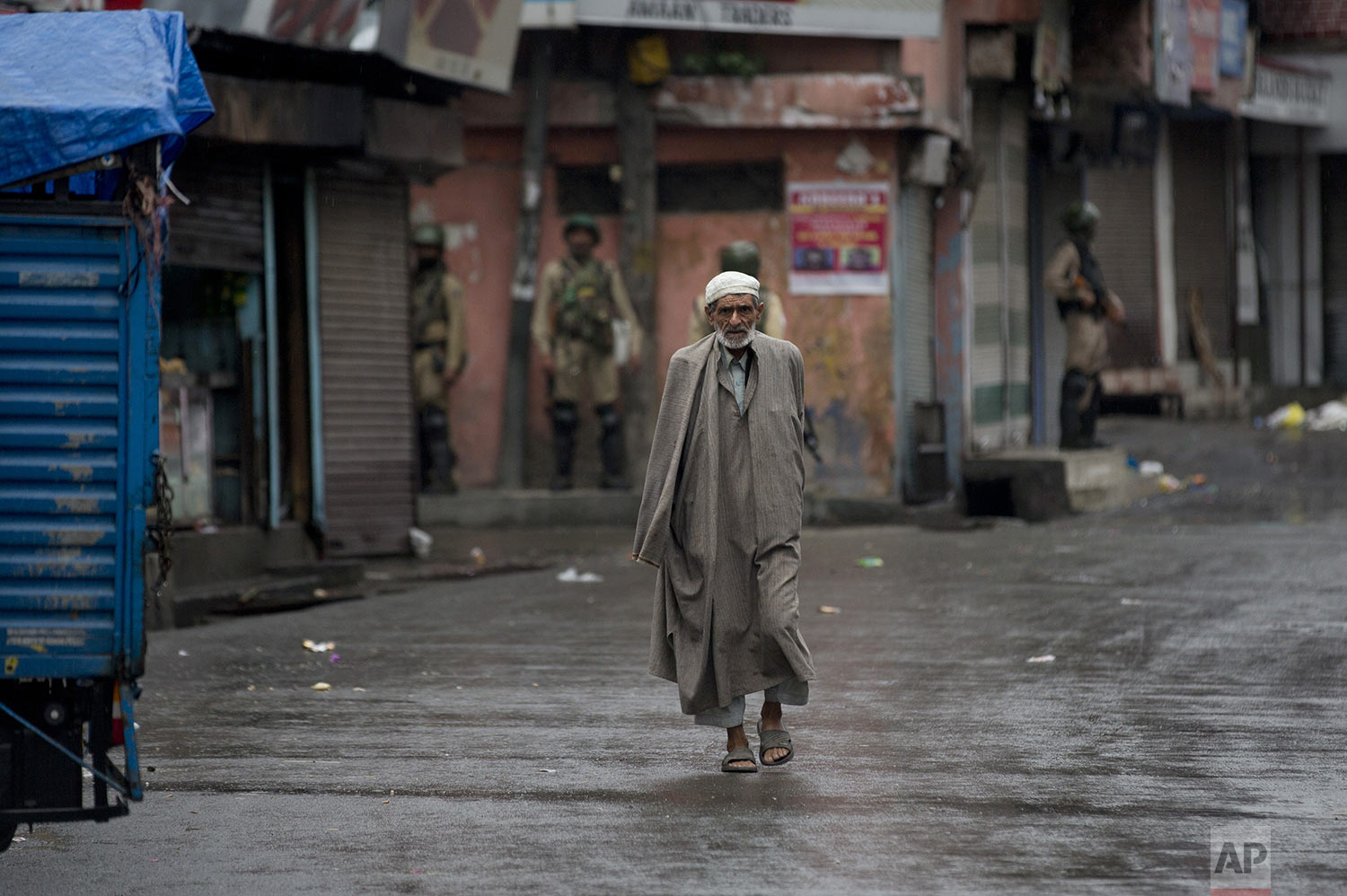 A Kashmiri man walks as Indian paramilitary soldiers stand guard during security lockdown in Srinagar, Indian controlled Kashmir, Wednesday, Aug. 14, 2019. (AP Photo/ Dar Yasin)