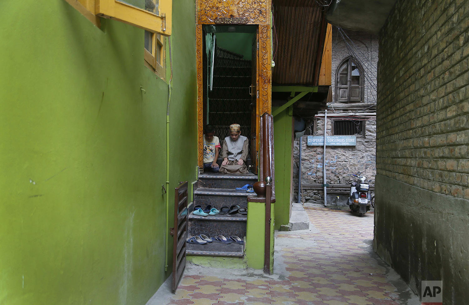 Kashmiri Muslim boys offer Friday prayers at the doorway of a local mosque in an alley during curfew like restrictions in Srinagar, India, Friday, Aug. 16, 2019. (AP Photo/Mukhtar Khan)