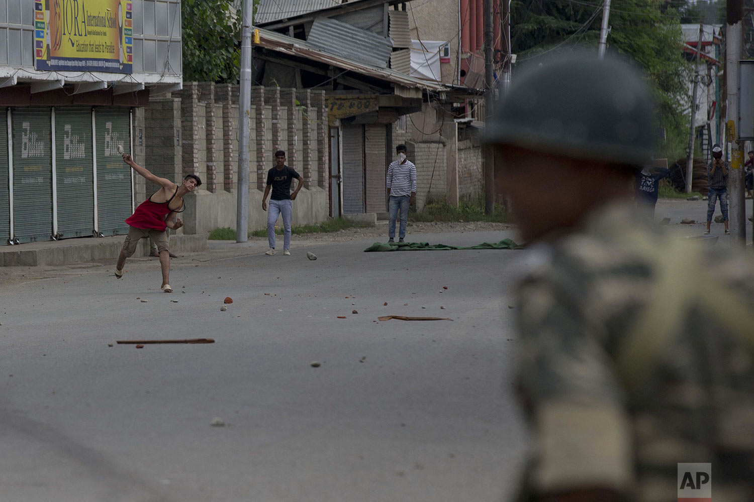 Kashmiri Muslim protesters throw stones at Indian paramilitary soldiers during curfew like restrictions in Srinagar, India, Friday, Aug. 16, 2019. (AP Photo/Dar Yasin)