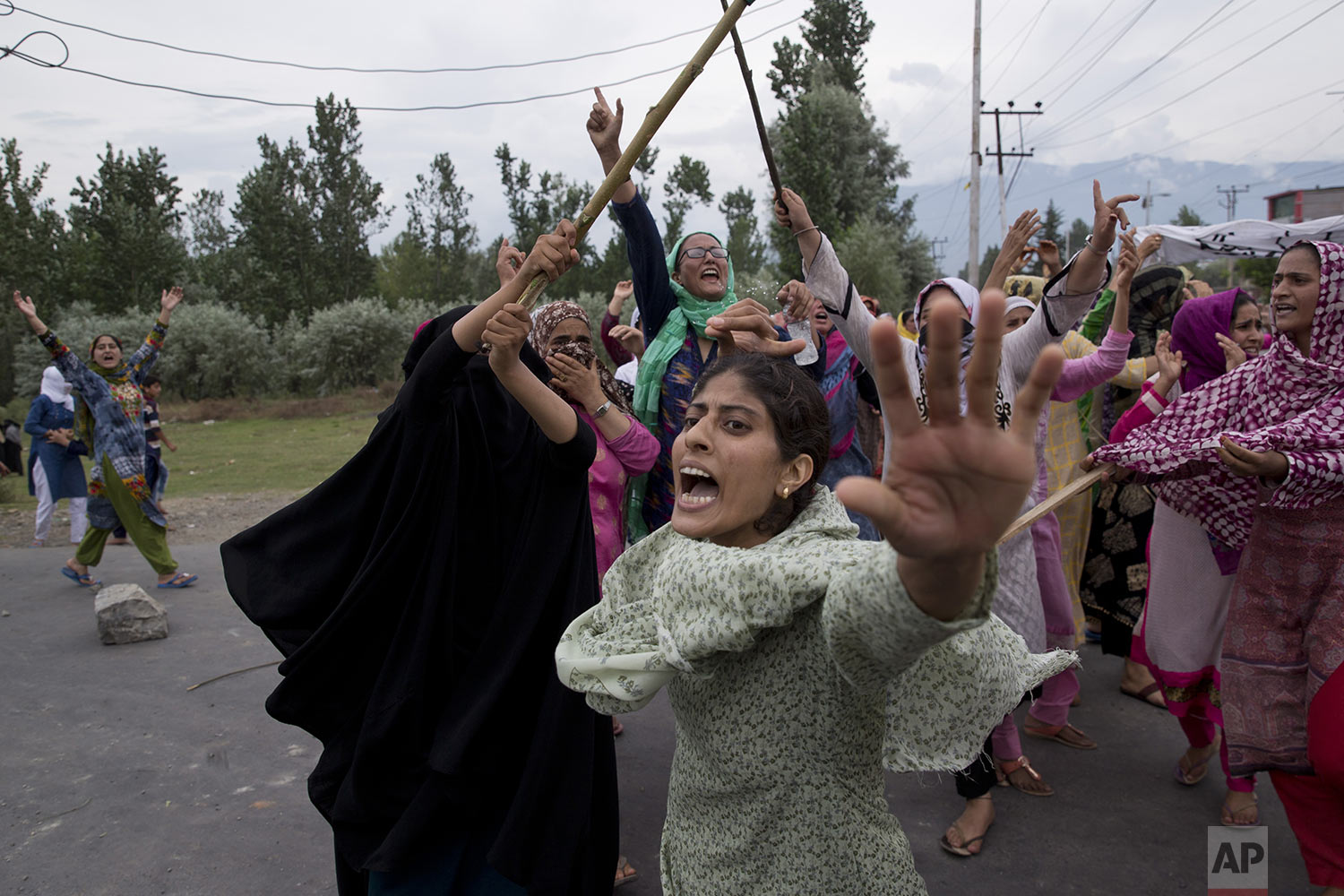 In this Friday, Aug. 9, 2019, photo, Kashmiri Muslim women shout slogans as Indian policemen fire teargas and live ammunition in the air to stop a protest march in Srinagar, Indian controlled Kashmir. (AP Photo/ Dar Yasin)