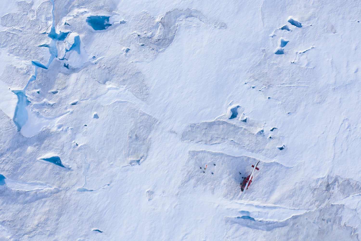 A helicopter carrying New York University air and ocean scientist David Holland and his team sits on the ice as they install a radar and GPS at the Helheim glacier, on Aug. 16, 2019, in Greenland. Scientists are hard at work there, trying to understand the alarmingly rapid melting of the ice. (AP Photo/Felipe Dana)