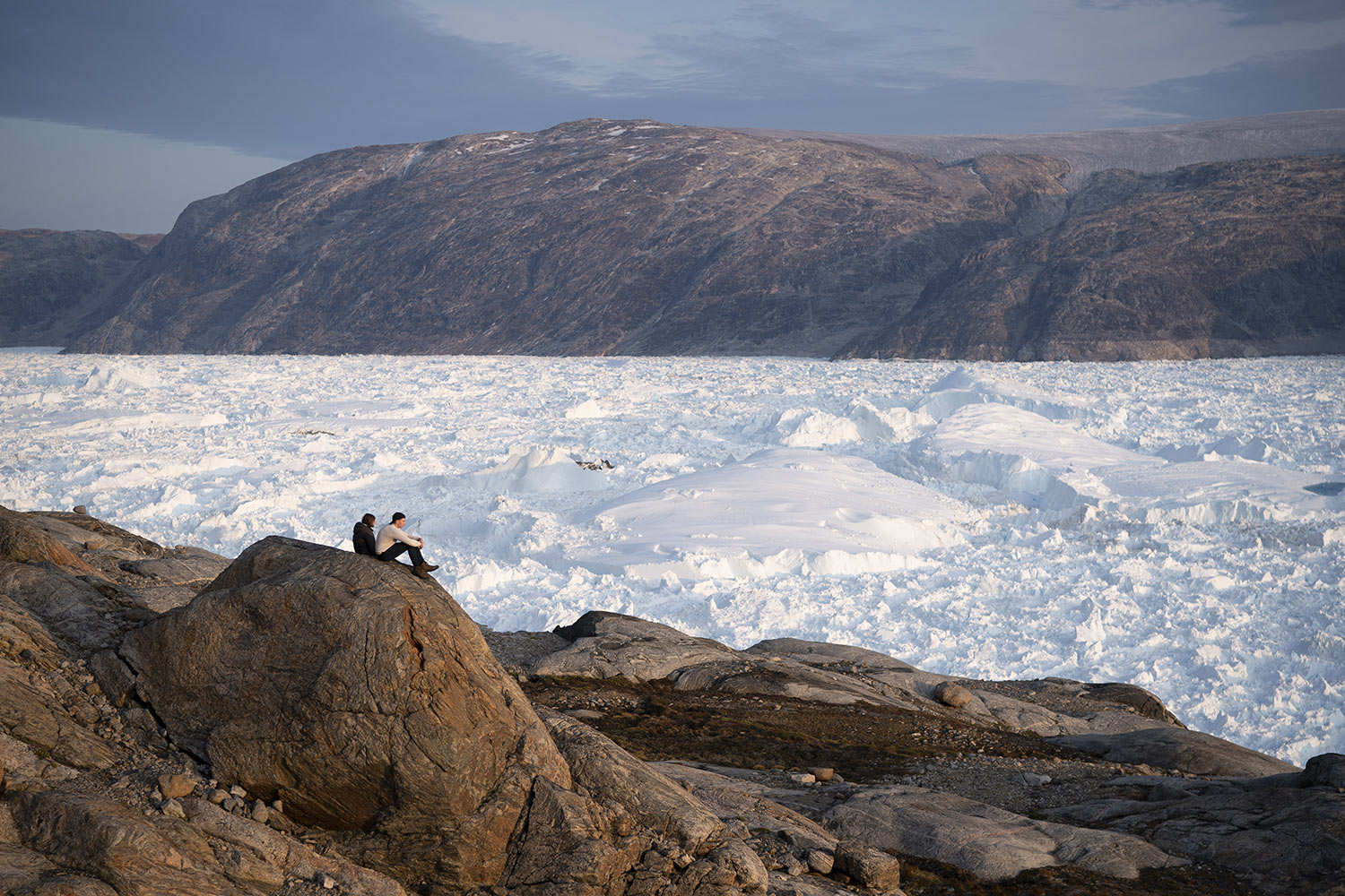 NYU student researchers sit on top of a rock overlooking the Helheim glacier on Aug. 16, 2019, in Greenland. Summer 2019 is hitting the island hard with record-shattering heat and extreme melt. Scientists estimate that by the end of the summer, about 440 billion tons of ice, maybe more, will have melted or calved off Greenland's giant ice sheet. Helheim glacier has shrunk about 6 miles (10 kilometers) since scientists visited in 2005. (AP Photo/Felipe Dana)