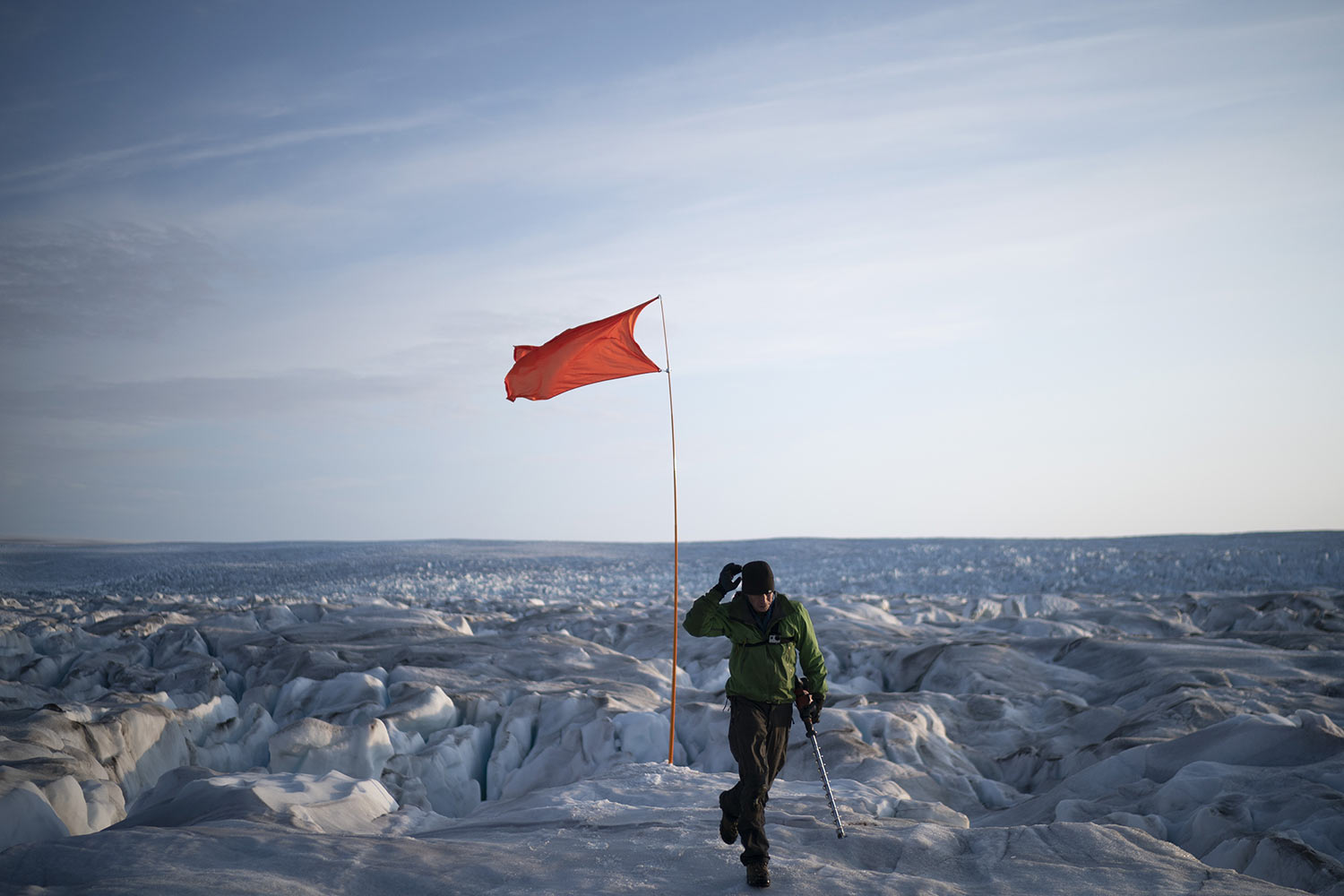 Brian Rougeux, NYU Field Safety Officer, walks after installing a flag to help identify a GPS position at the Helheim glacier, on Aug. 16, 2019, in Greenland. Summer 2019 is hitting the island hard with record-shattering heat and extreme melt. (AP Photo/Felipe Dana)