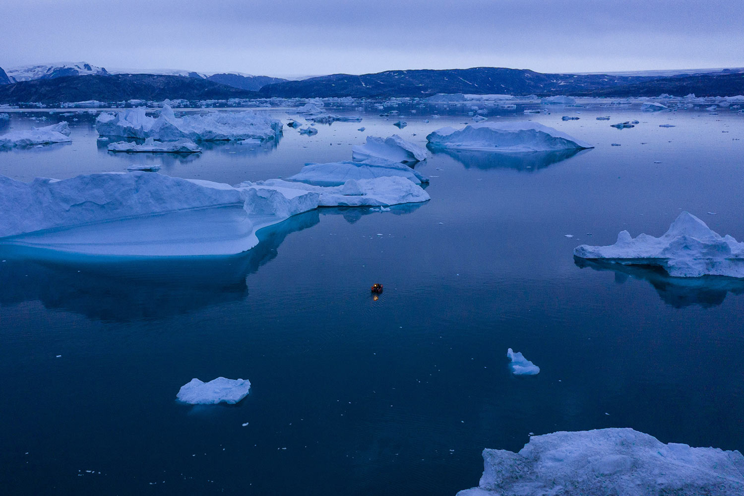 A boat navigates at night between icebergs in eastern Greenland, Aug. 15, 2019. Greenland has been melting faster in the last decade and this summer, it has seen two of the biggest melts on record since 2012. (AP Photo/Felipe Dana)