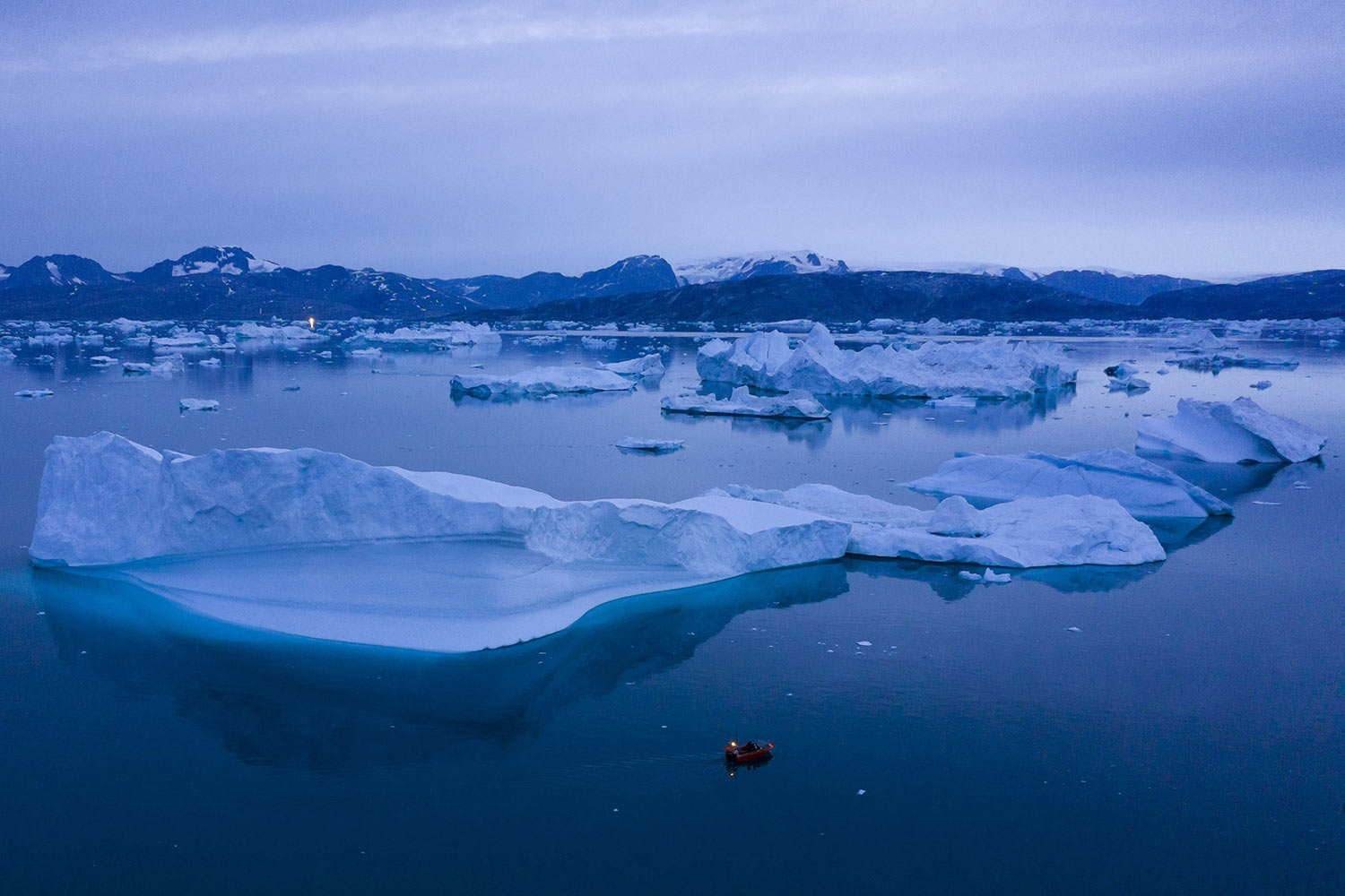 A boat navigates at night next to large icebergs near the town of Kulusuk, on Aug. 15, 2019, in eastern Greenland. Greenland's ice has been melting for more than 20 years, but in 2019, it's as if Earth's refrigerator door has been left open, and it means a potentially large rise in the world's sea levels. (AP Photo/Felipe Dana)