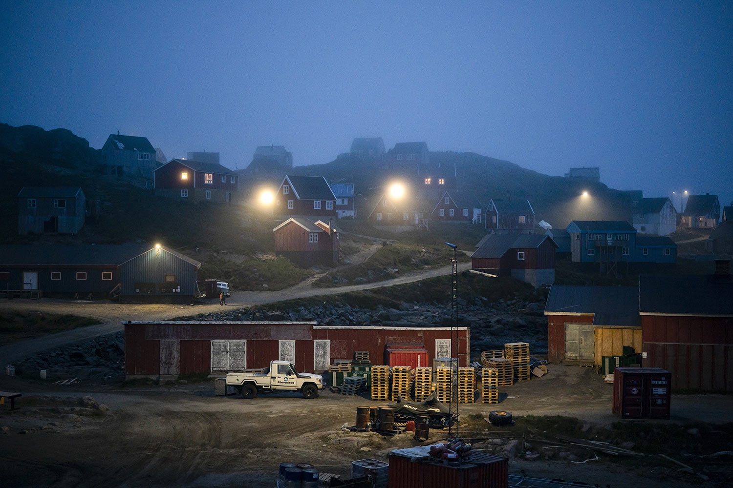 Early morning fog shrouds homes on Aug. 15, 2019, in Kulusuk, Greenland. In tiny Kulusuk, resident Mugu Utuaq says the winter that used to last as long as 10 months when he was a boy, can now be as short as five months. Scientists are hard at work in Greenland, trying to understand the alarmingly rapid melting of the ice. (AP Photo/Felipe Dana)