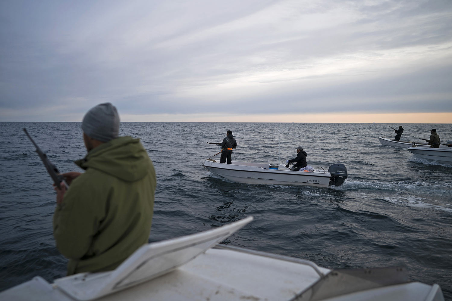 Mugu Utuaq, left, reloads his rifle as he rides with other boats hunting whales on Aug. 16, 2019, near Kulusuk, Greenland. Summer in 2019 is hitting the island hard with record-shattering heat and extreme melt. Scientists estimate that by the end of the summer, about 440 billion tons of ice, maybe more, will have melted or calved off Greenland's giant ice sheet. (AP Photo/Felipe Dana)