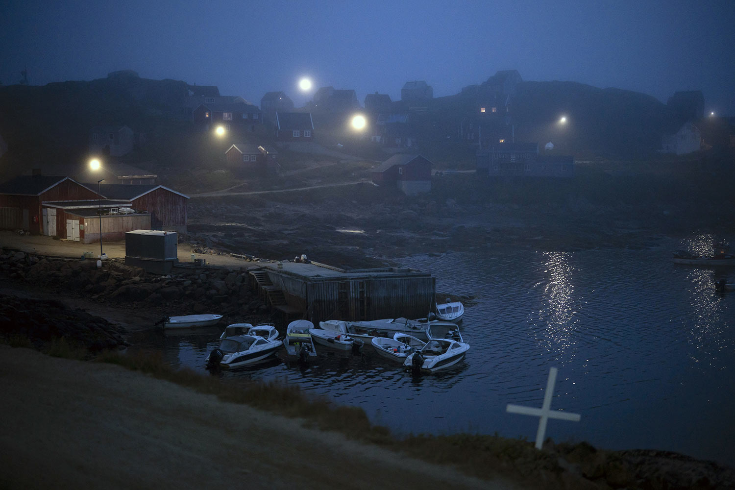 A cross sits on the side of the road as fog covers homes in Kulusuk, Greenland, early Thursday, Aug. 15, 2019. Greenland has been melting faster in the last decade and this summer, it has seen two of the biggest melts on record since 2012. (AP Photo/Felipe Dana)