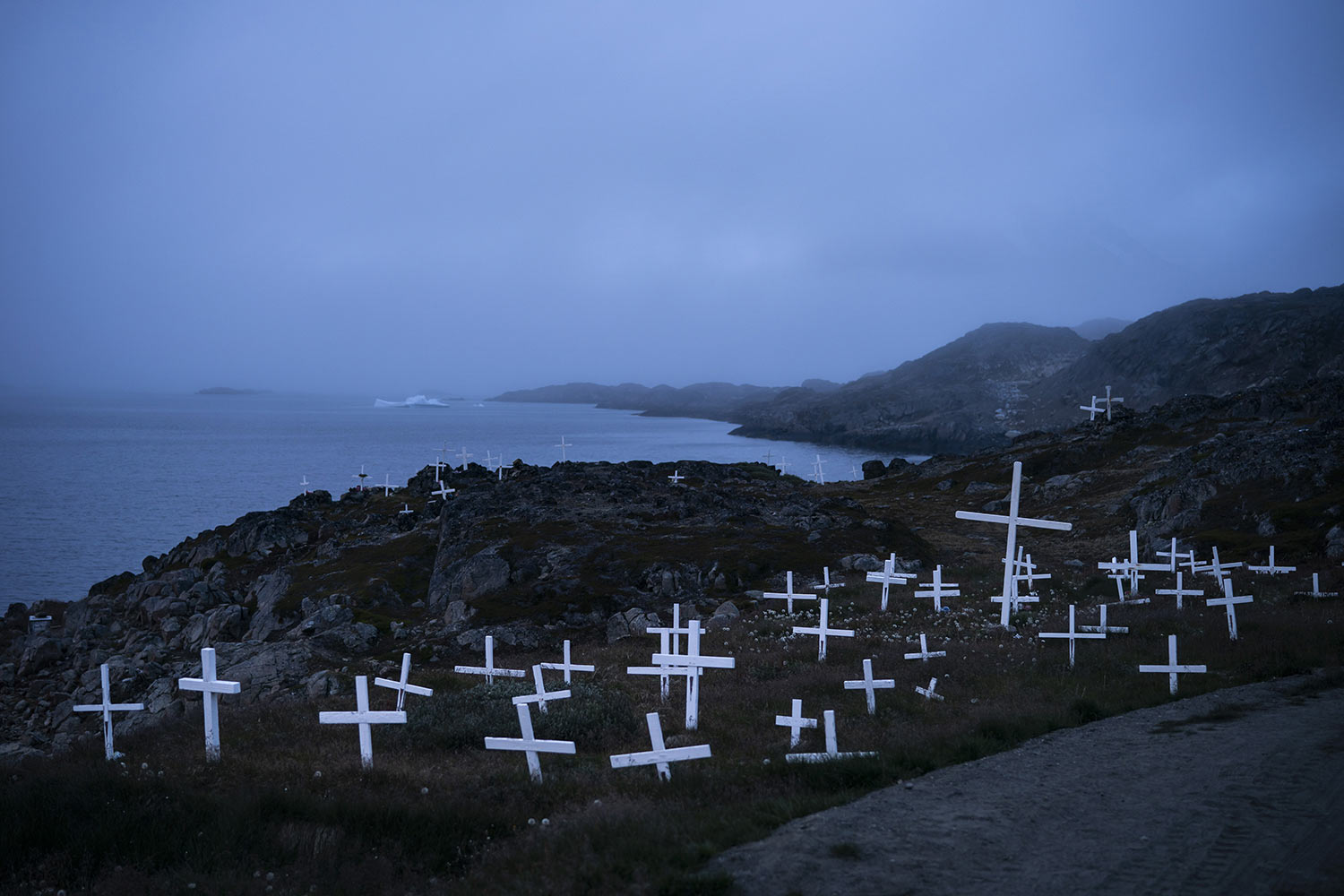 Crosses stand in a cemetery as an iceberg floats in the distance during a foggy morning on Aug. 15, 2019, in Kulusuk, Greenland. Kulusuk's resident Mugu Utuaq says the winter that used to last for as long as 10 months when he was a boy can now be as short as five months. Scientists are hard at work in Greenland, trying to understand the alarmingly rapid melting of the ice. (AP Photo/Felipe Dana)