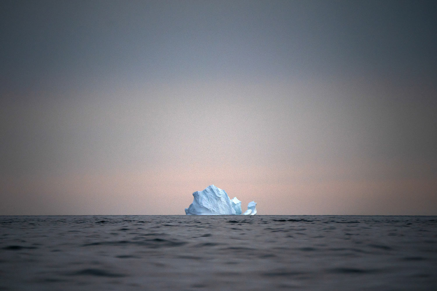 A large Iceberg floats away as the sun sets on Aug. 15, 2019, near Kulusuk, Greenland. Greenland is where Earth's refrigerator door is left open, where glaciers dwindle and seas begin to rise. Scientists are hard at work there, trying to understand the alarmingly rapid melting of the ice. For Greenland is where the planet's future is being written. (AP Photo/Felipe Dana)