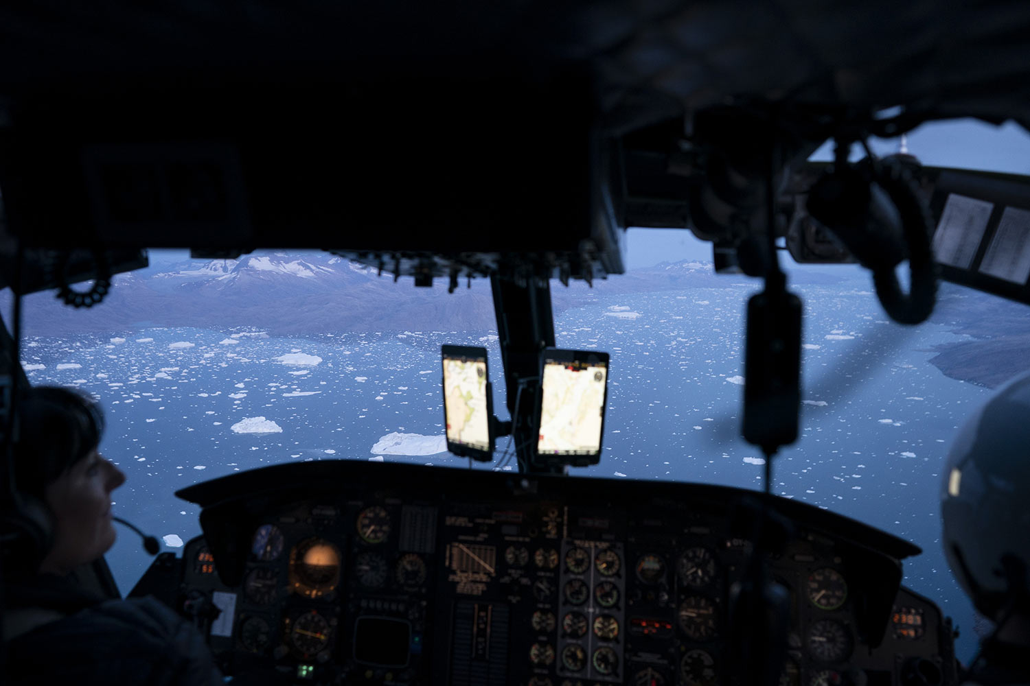 A helicopter flies over hundreds of icebergs floating near the Helheim glacier, on Aug. 16, 2019, in Greenland. Summer 2019 is hitting the island hard with record-shattering heat and extreme melt. Scientists estimate that by the end of the summer, about 440 billion tons of ice, maybe more, will have melted or calved off Greenland's giant ice sheet. Helheim glacier has shrunk about 6 miles (10 kilometers) since scientists visited in 2005. (AP Photo/Felipe Dana)