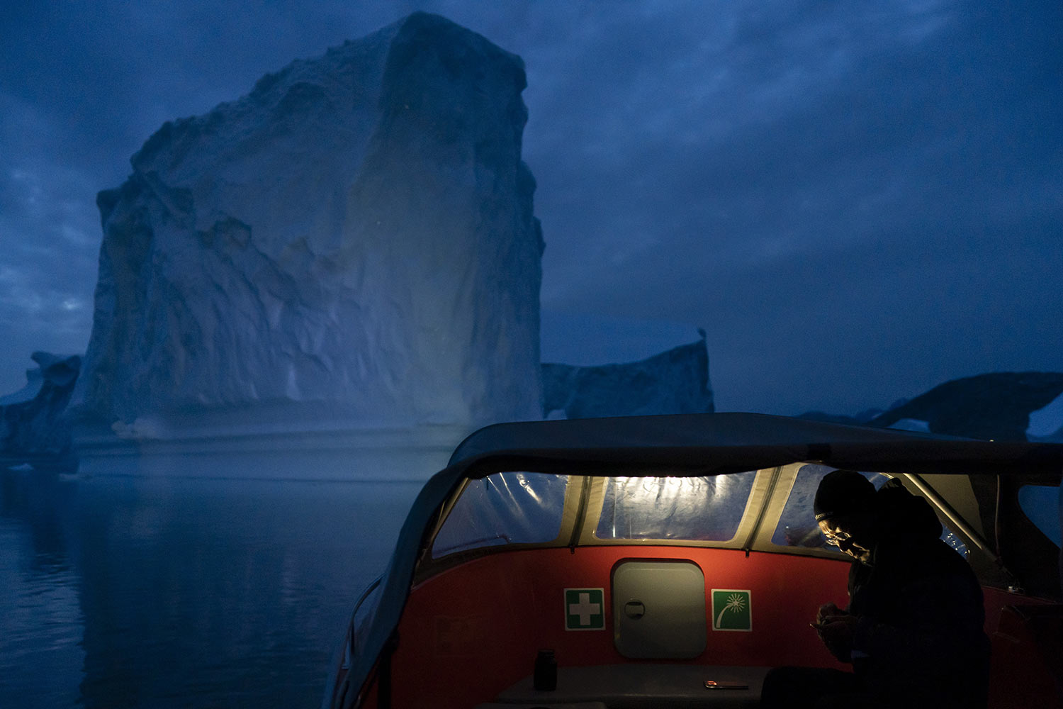A boat navigates at night next to a large iceberg on Aug. 15, 2019, in eastern Greenland. Summer 2019 is hitting Greenland hard with record-shattering heat and extreme melt. By the end of the summer, about 440 billion tons (400 billion metric tons) of ice, maybe more, will have melted or calved off Greenland's giant ice sheet, scientists estimate. (AP Photo/Felipe Dana)