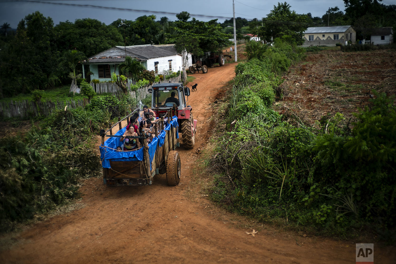 In this Aug. 24, 2019 photo, a tractor pulls a trailer converted into a swimming pool along the roads of El Infernal neighborhood in San Andres in the province of Pinar del Río, Cuba. (AP Photo/Ramon Espinosa)