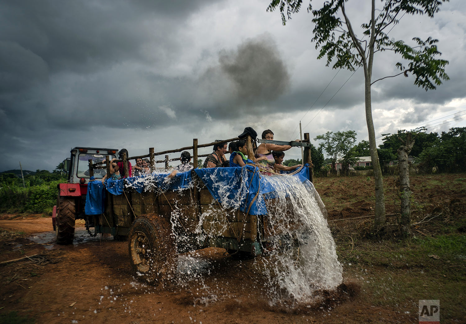 In this Aug. 24, 2019 photo, a tractor pulls a trailer that was converted into a swimming pool as it drives along the roads of El Infernal neighborhood in San Andres in the province of Pinar del Río, Cuba.  (AP Photo/Ramon Espinosa)