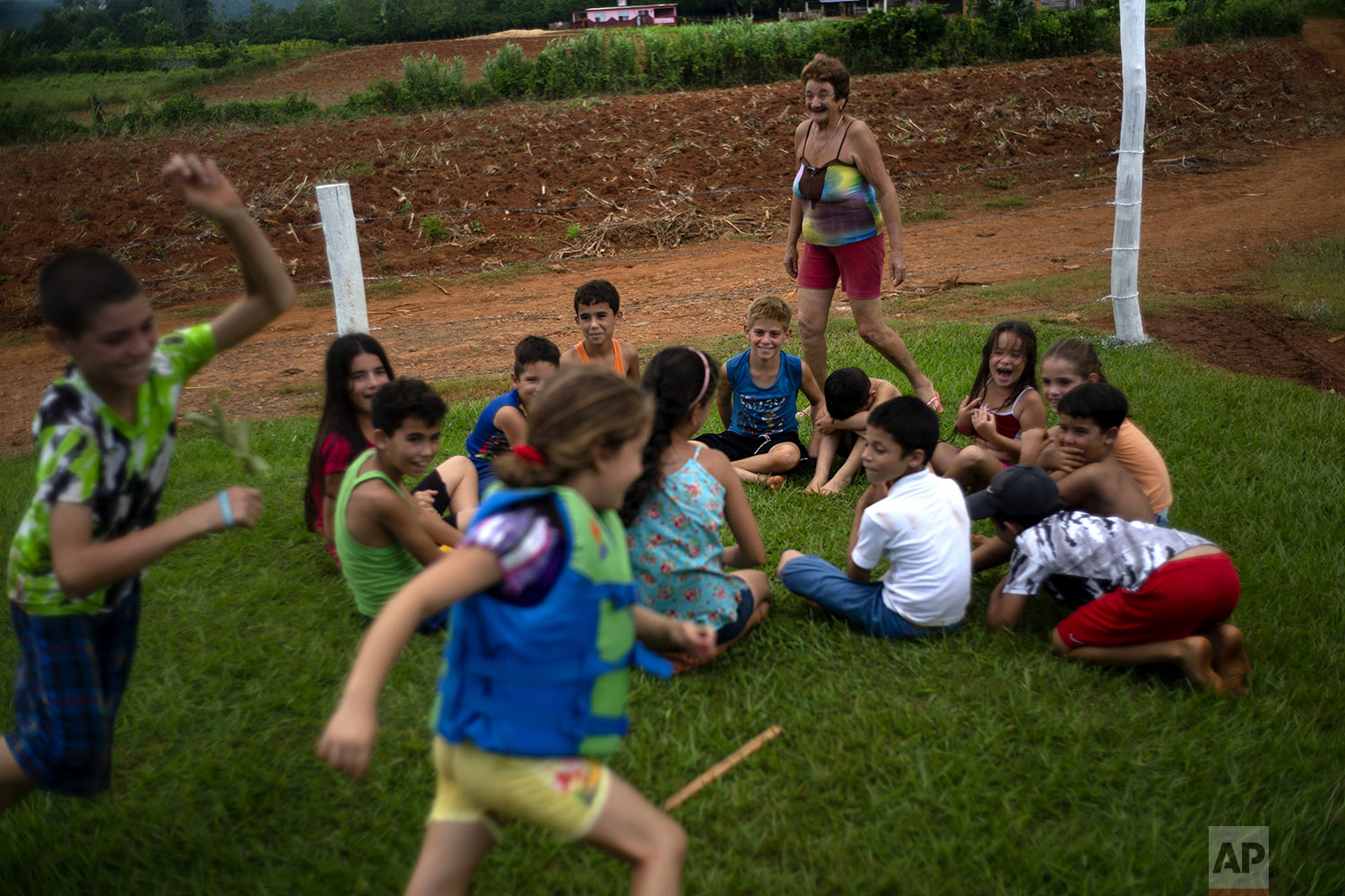 In this Aug. 24, 2019 photo, children play as they wait for a tractor trailer to be converted into a swimming pool in El Infernal neighborhood in San Andres in the province of Pinar del Río, Cuba. (AP Photo/Ramon Espinosa)