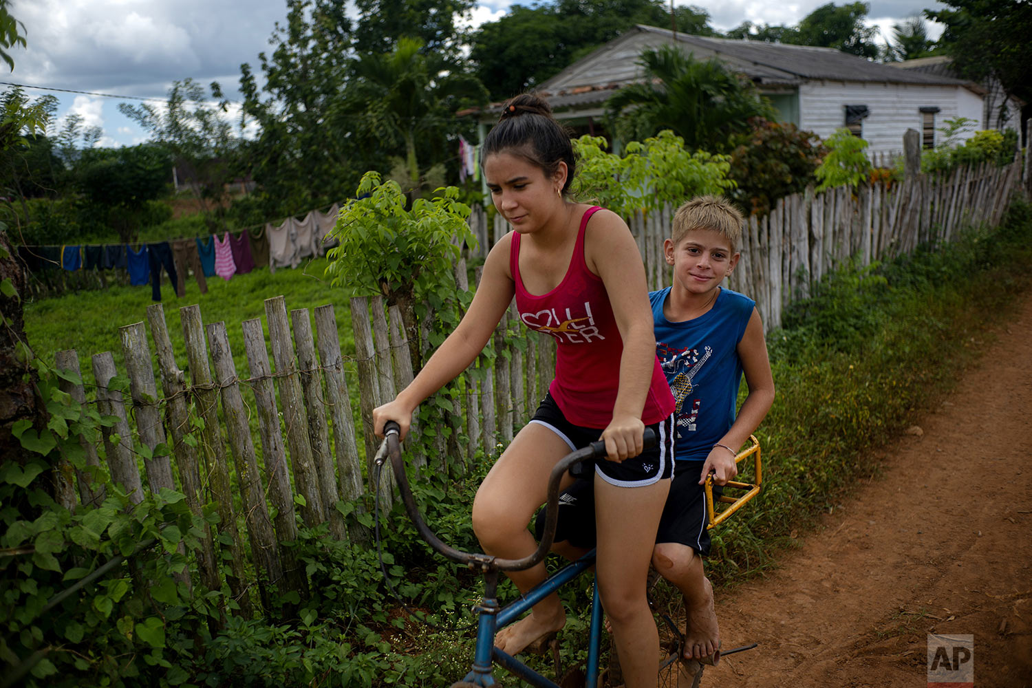 In this Aug. 24, 2019 photo, children cycle to a tractor trailer that has been converted into a swimming pool in El Infernal neighborhood in San Andres in the province of Pinar del Río, Cuba. (AP Photo/Ramon Espinosa)
