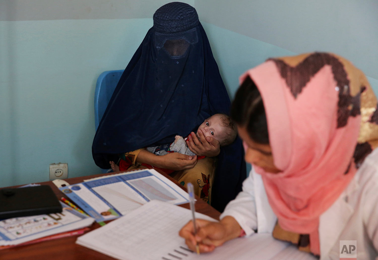 A woman holds her son, Abdullah, who is suffering from malnutrition as a doctor writes a prescription for him at a UNICEF clinic in Jabal Saraj north of Kabul, Afghanistan, Aug. 26, 2019. Days ago, he was at an emergency ward. (AP Photo/Rafiq Maqbool)