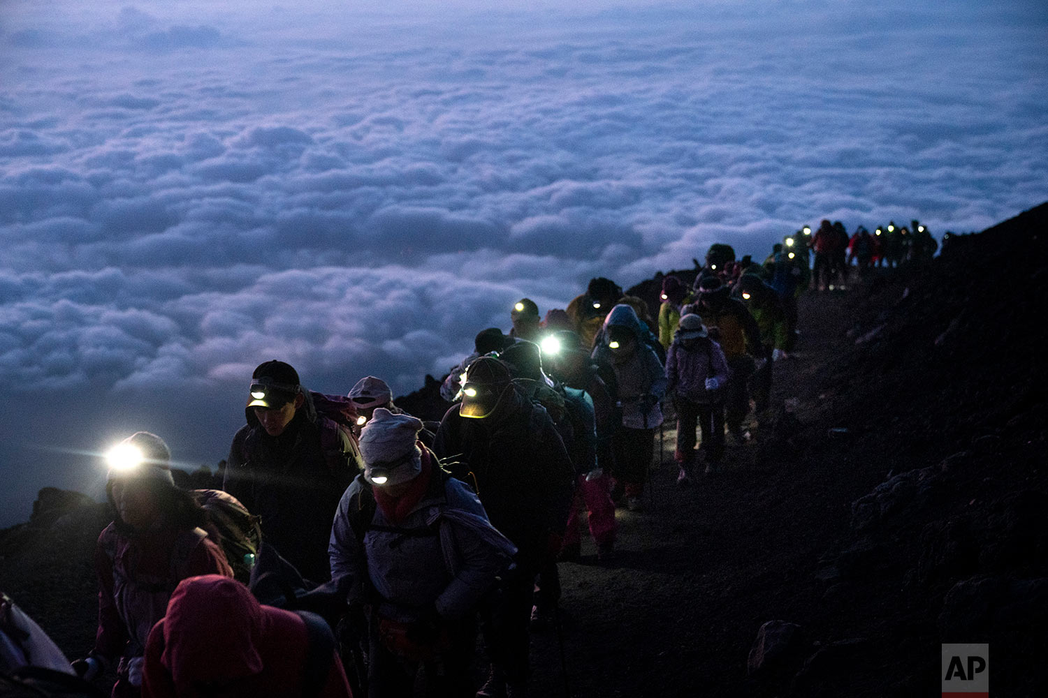 A group of hikers climb to the top of Mount Fuji just before sunrise as clouds hang below the summit Aug. 27, 2019, in Japan. (AP Photo/Jae C. Hong)