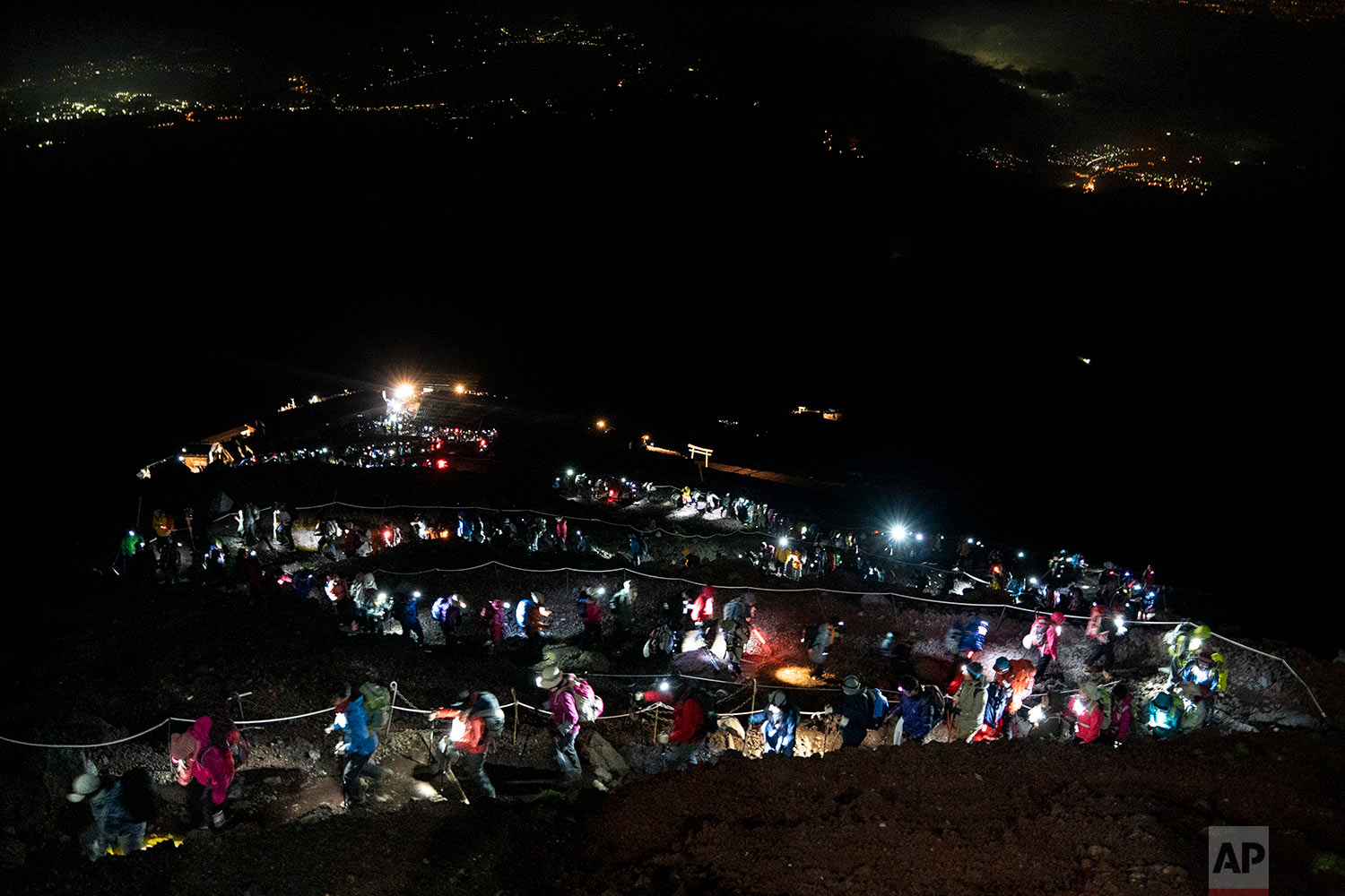 Hundreds of climbers wearing headlamps form a long line as they climb to the summit of Mount Fuji to watch the sunrise, Aug. 3, 2019, in Japan. (AP Photo/Jae C. Hong)