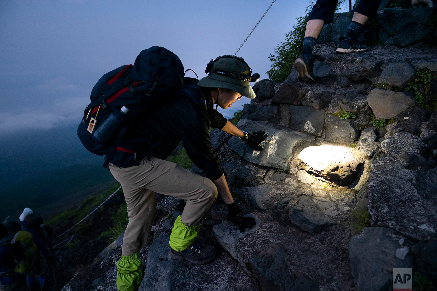 A man with a headlamp climbs to the summit of Mount Fuji, Aug. 2, 2019, in Japan. (AP Photo/Jae C. Hong)