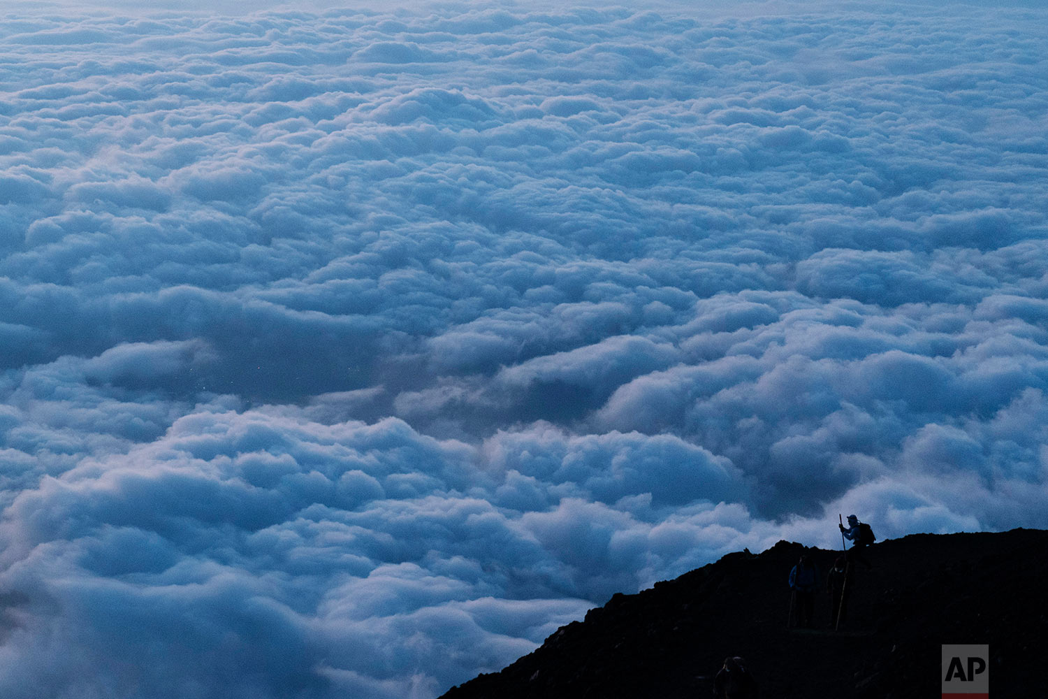 A climber stops to take pictures of clouds while climbing towards the summit of Mount Fuji to watch the sunrise, Aug. 27, 2019, in Japan. (AP Photo/Jae C. Hong)