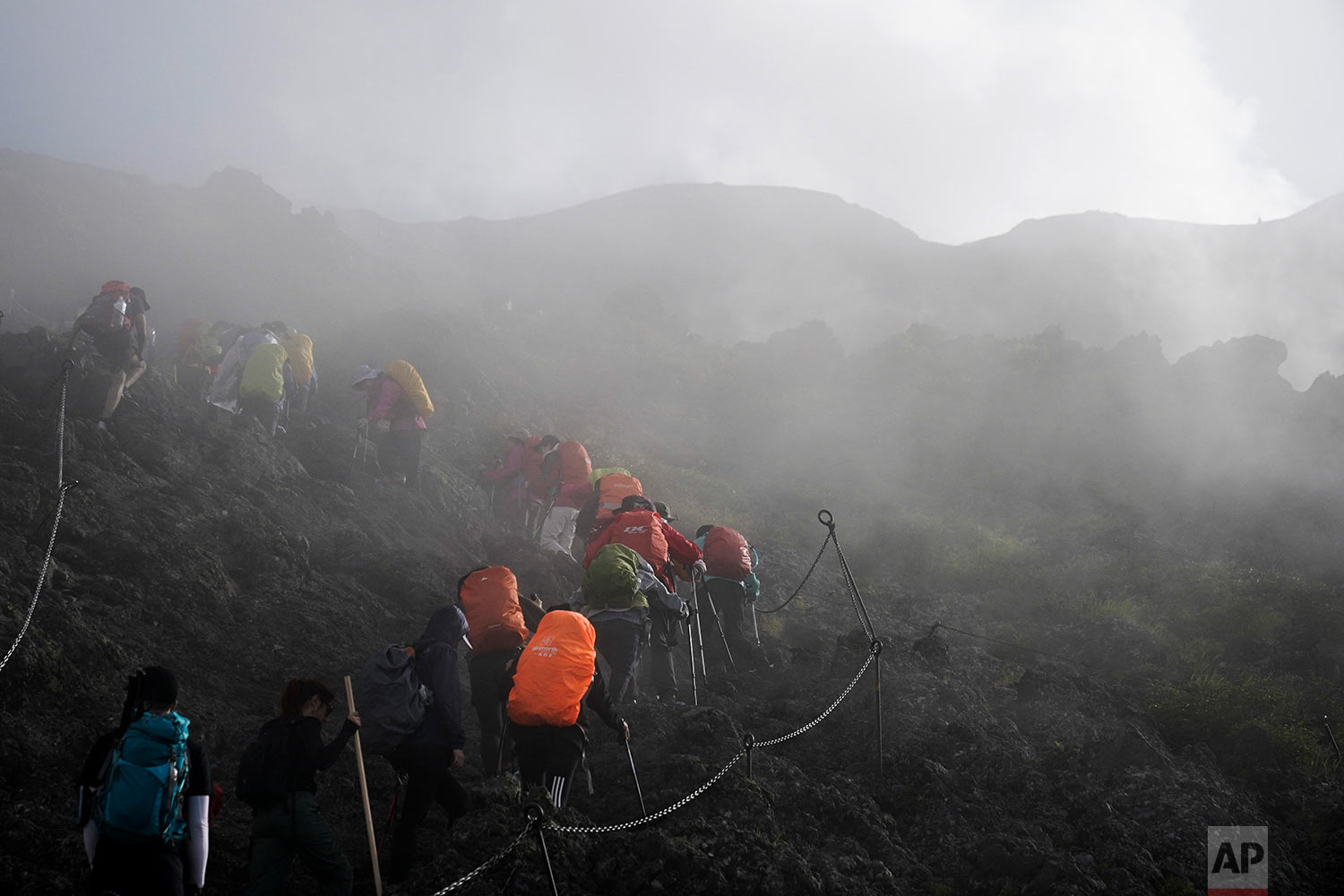 people climb through a dense fog as they make their way along the Yoshida trail towards the summit of Mount Fuji, Aug. 26, 2019, in Japan. (AP Photo/Jae C. Hong)