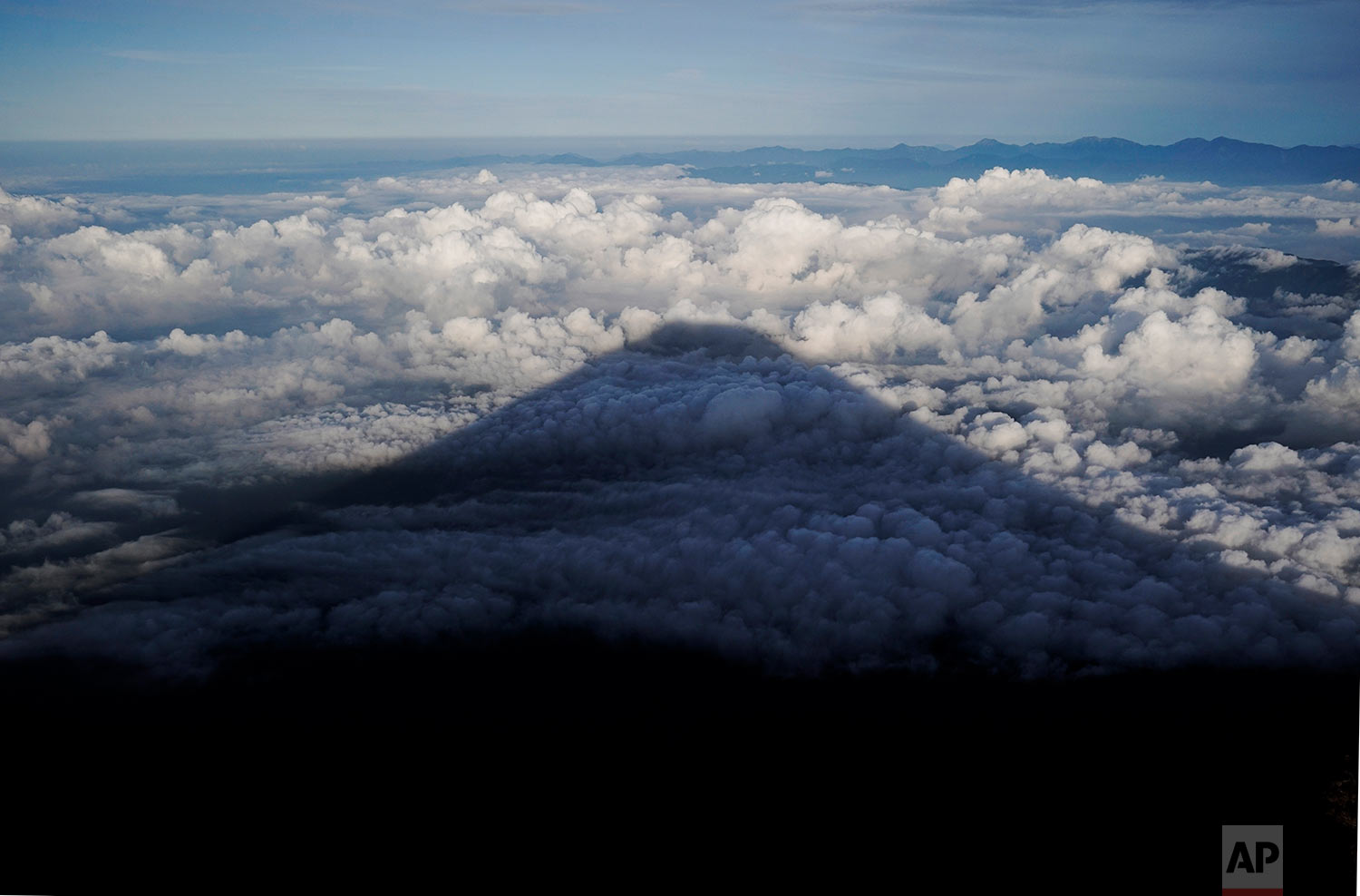 The shadow of Mount Fuji is casted on clouds hanging below the summit, Aug. 27, 2019, in Japan. (AP Photo/Jae C. Hong)