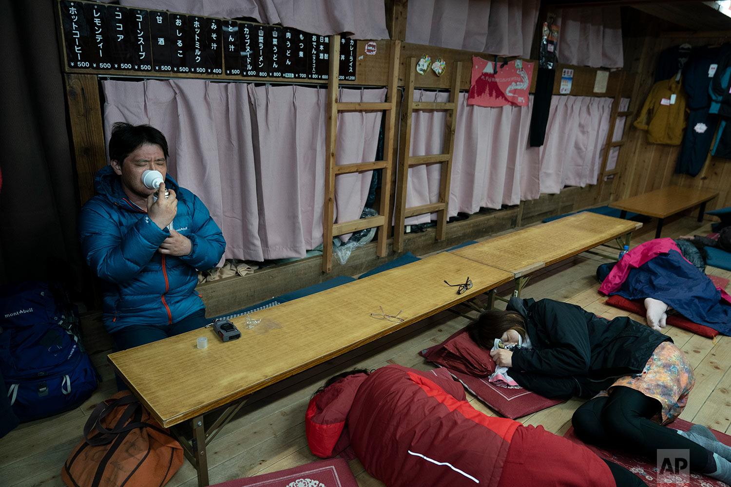 A man inhales oxygen from a can in a mountain hut while getting ready to climb to the summit of Mount Fuji to watch the sunrise, Aug. 3, 2019, in Japan. (AP Photo/Jae C. Hong)