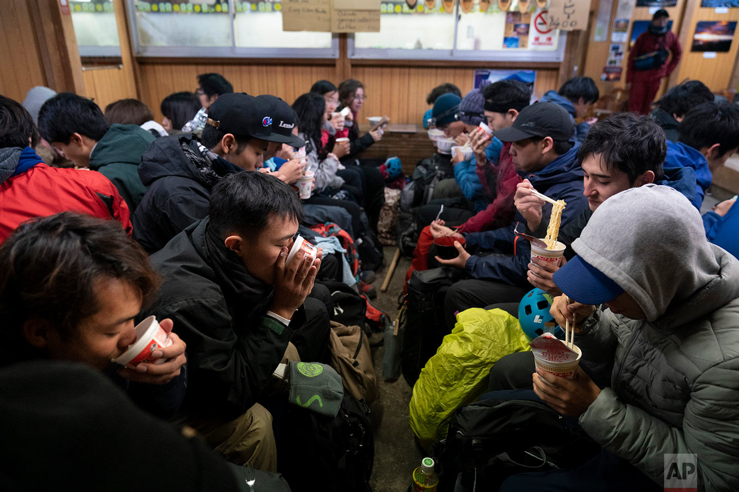 Waiting for the sunrise, climbers eat noodles in a restaurant located on the summit of Mount Fuji, Aug. 27, 2019, in Japan. (AP Photo/Jae C. Hong)
