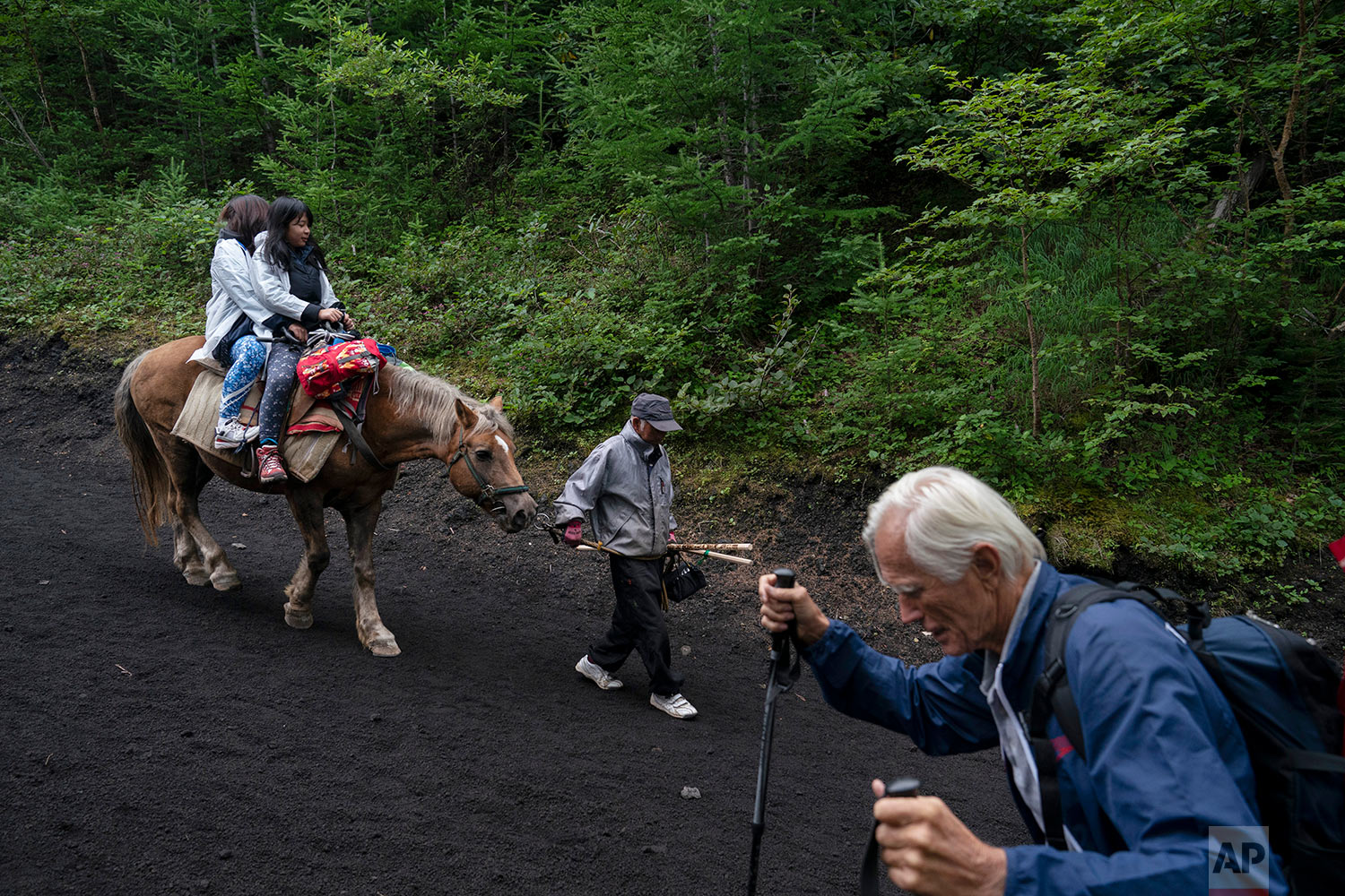 Two climbers on a horse descend the Yoshida trail of Mount Fuji, Aug. 26, 2019, in Japan. (AP Photo/Jae C. Hong)