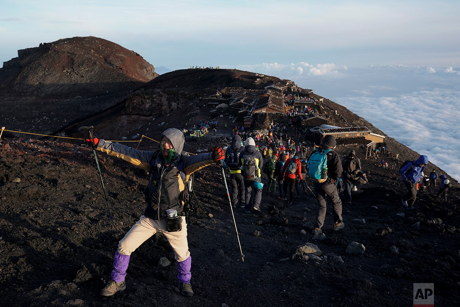 A climber poses for photos after watching the sunrise on the summit of Mount Fuji in Japan, Aug. 27, 2019. (AP Photo/Jae C. Hong)
