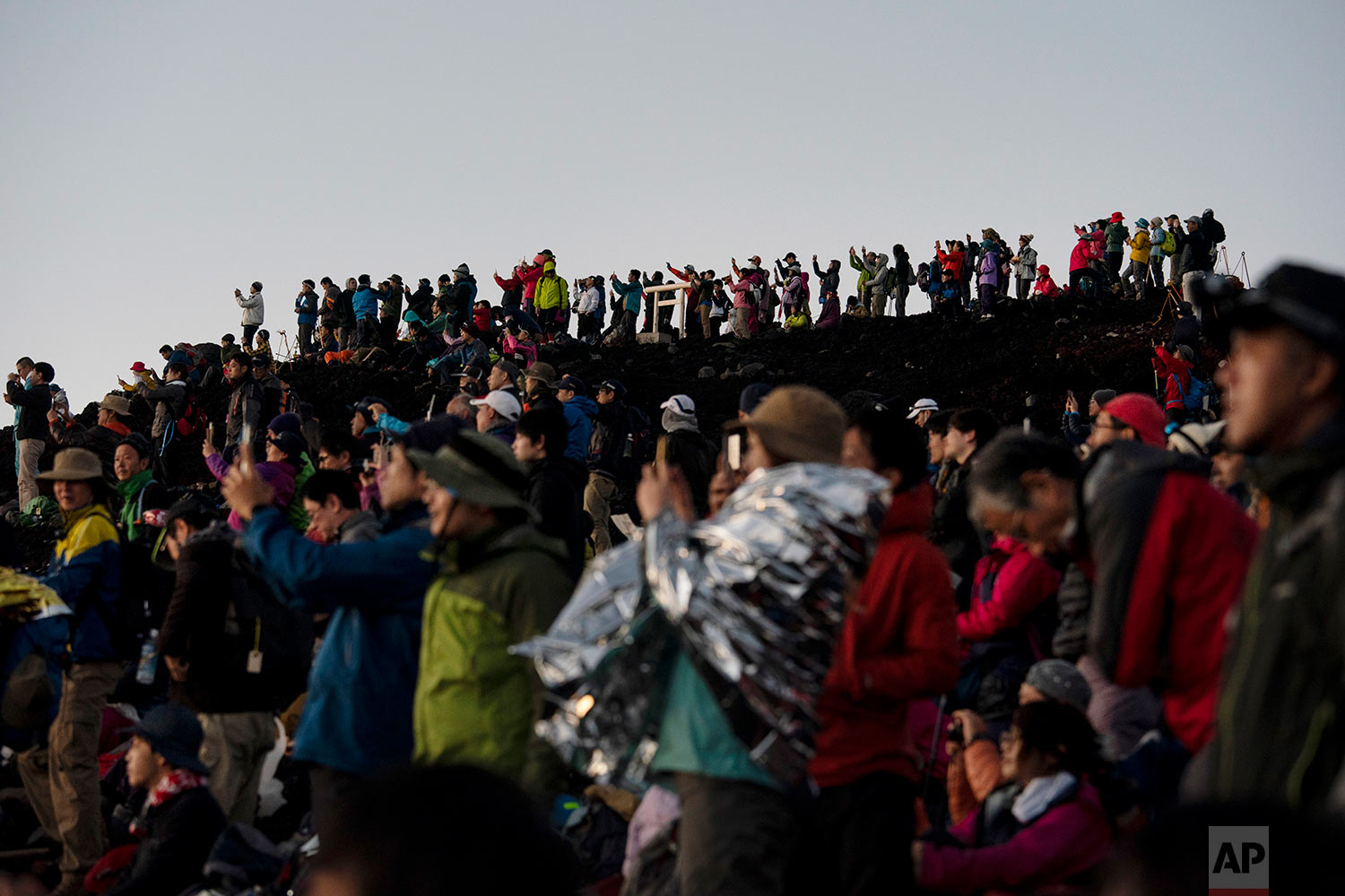 Hundreds of climbers watch the sunrise from the summit of Mount Fuji in Japan, Aug. 3, 2019. (AP Photo/Jae C. Hong)
