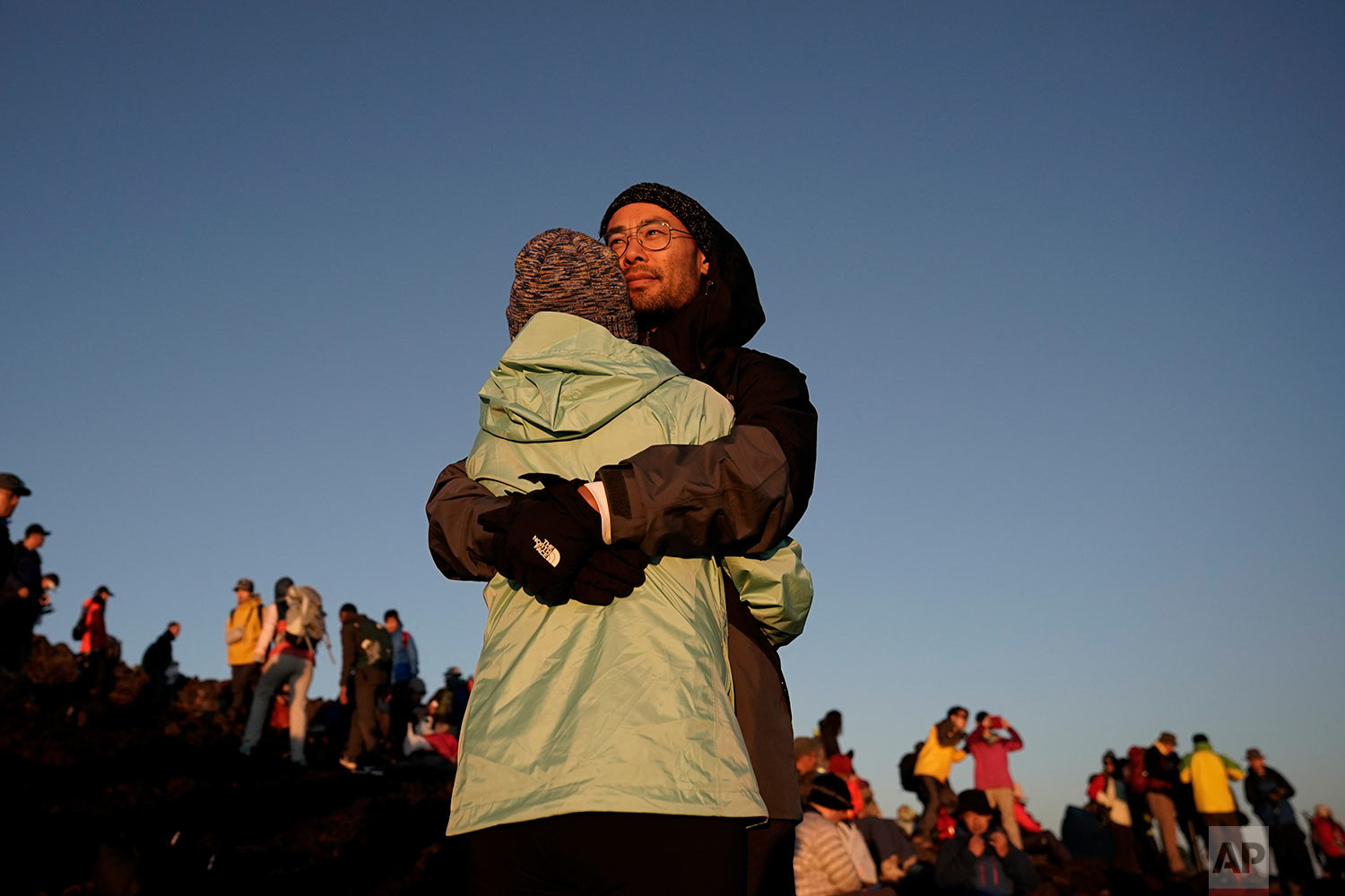 A couple hugs while watching the sunrise from the summit of Mount Fuji, Aug. 3, 2019, in Japan. (AP Photo/Jae C. Hong)