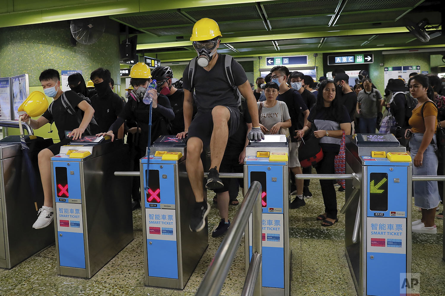 Protesters jump over MTR gates as they move to another destination during the anti-extradition bill protest in Hong Kong, Sunday, Aug. 11, 2019.  (AP Photo/Kin Cheung)