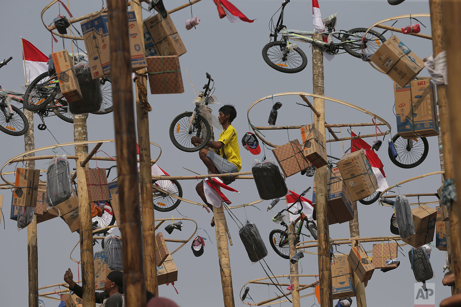 An Indonesian man retrieves his prize after climbing up a greased pole during a greased-pole climbing competition held as part of Independence Day celebrations at Ancol Beach in Jakarta, Indonesia, Saturday, Aug. 17, 2019. (AP Photo/Tatan Syuflana)