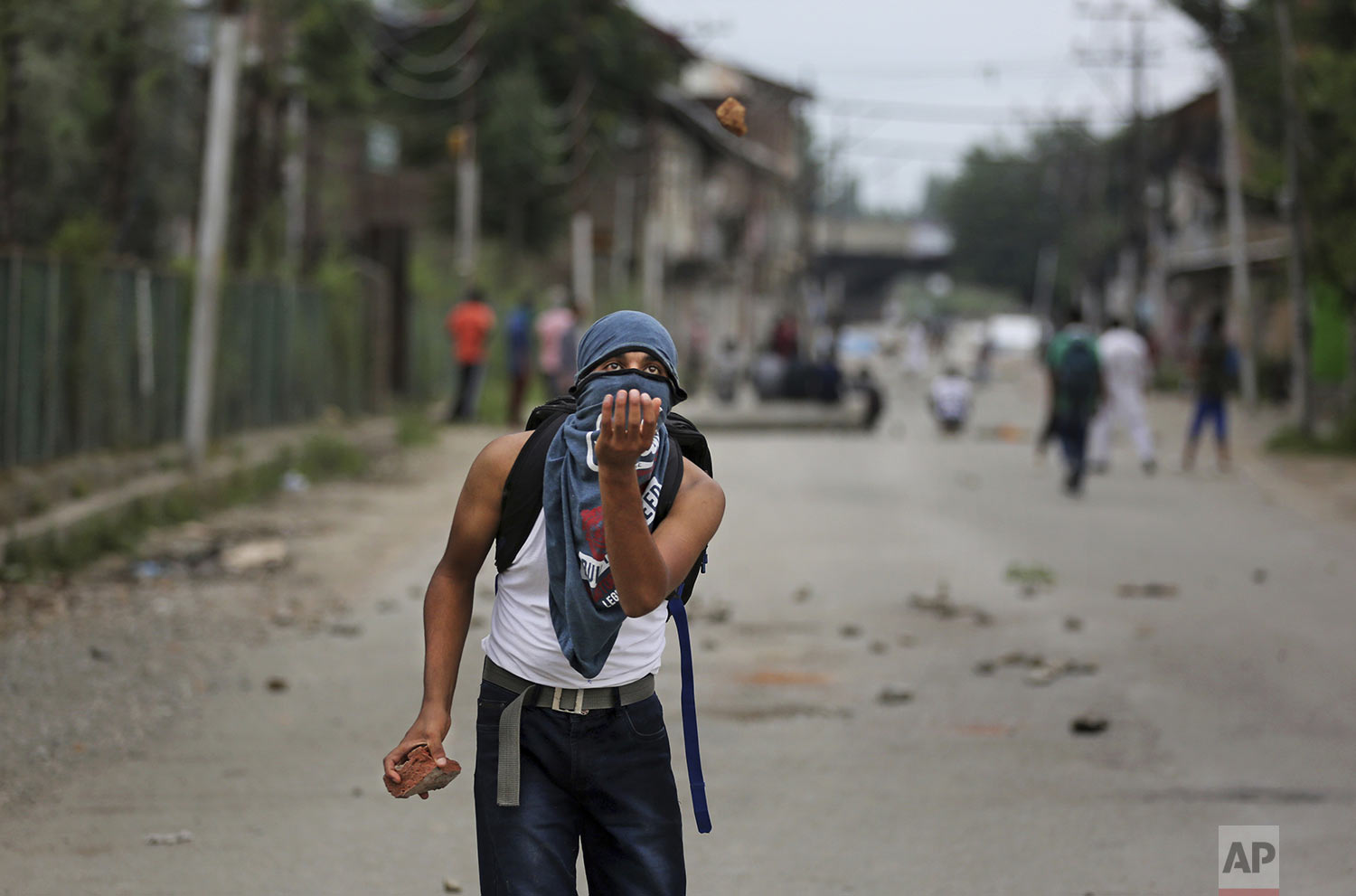A Kashmiri prepares to catch a stone during an anti-India protest Srinagar, India, Friday, Aug. 9, 2019 (AP Photo/Altaf Qadri)