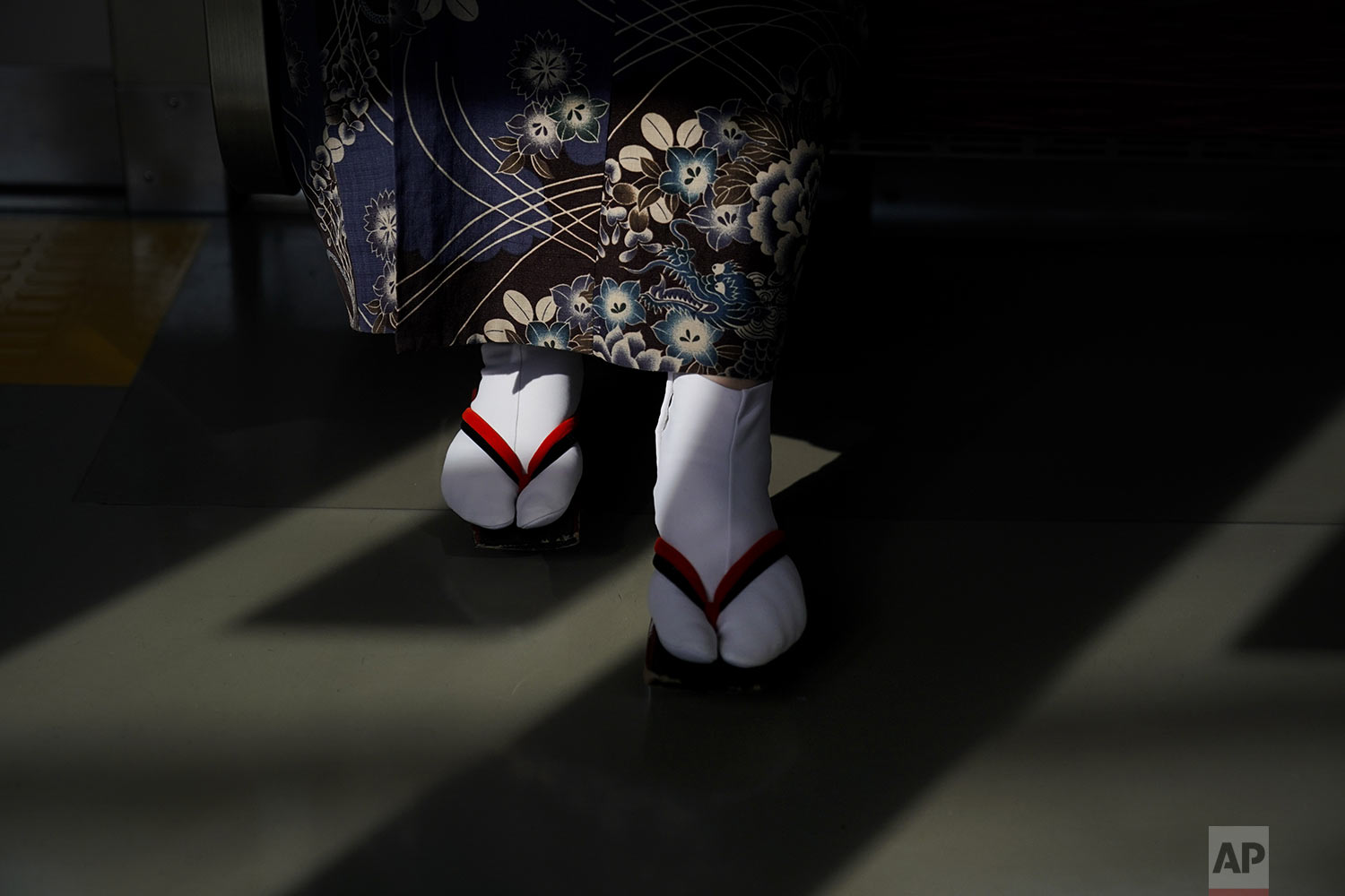 "A woman wearing a kimono and traditional Japanese sandals called ""geta"""" is lit by the afternoon sunlight coming through the window of a train, in Kawagoe, near Tokyo, Friday, Aug. 16, 2019. (AP Photo/Jae C. Hong)"