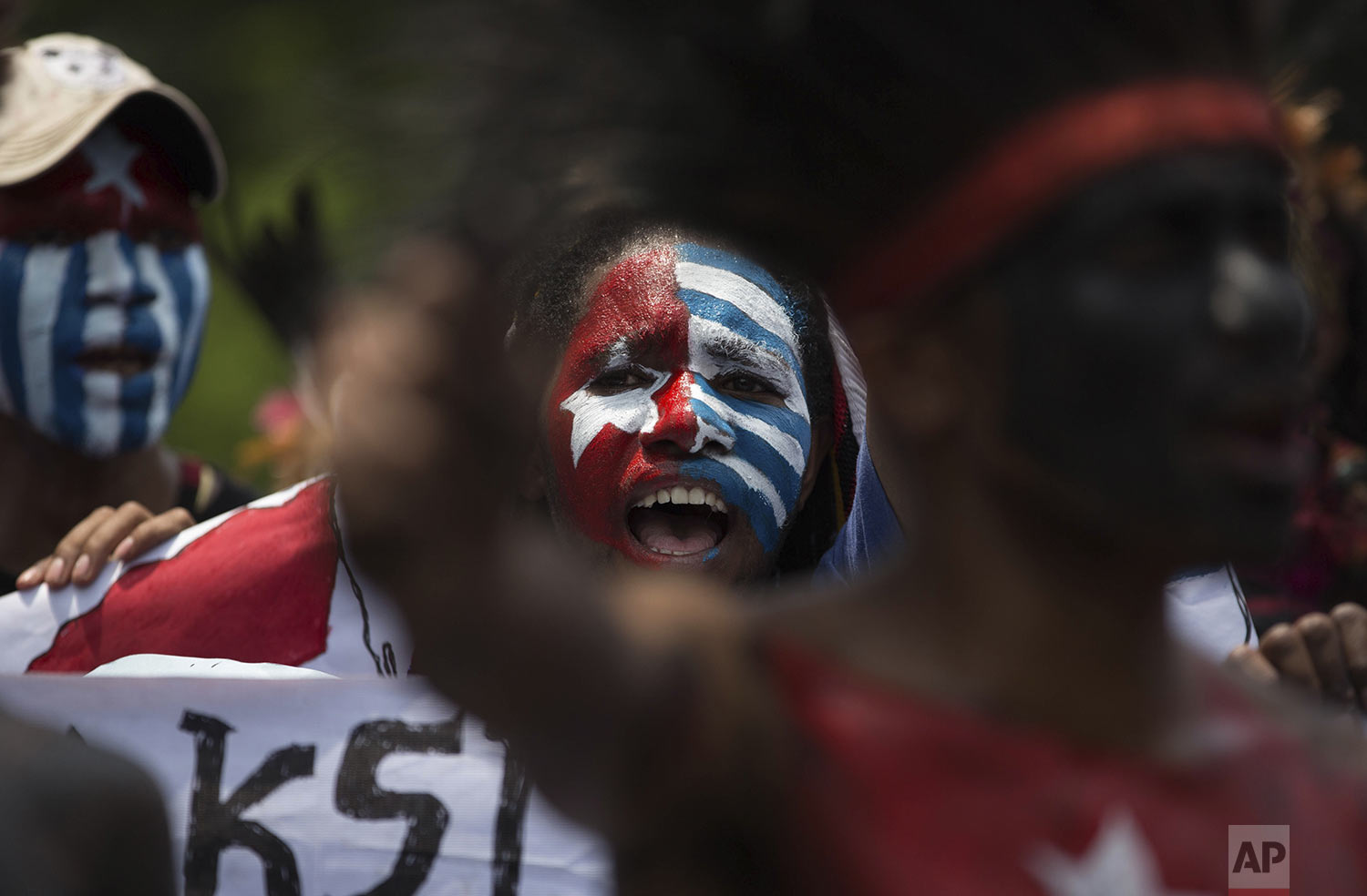 Papuan students, with their body and face painted with the colors of the banned separatist 'Morning Star' flag, shout slogans during a rally in Medan, North Sumatra, Indonesia, Saturday, Aug. 31, 2019. (AP Photo/Binsar Bakkara)