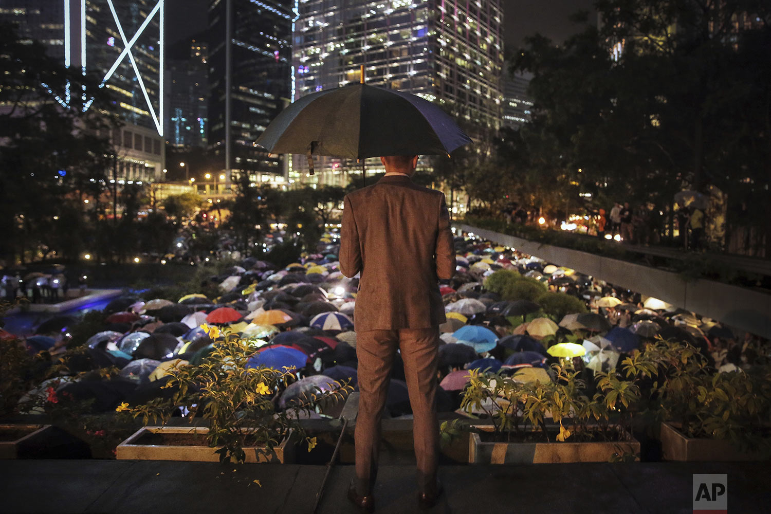 A man holding an umbrella looks at people with umbrellas gathered at Chater Garden to give support to the recent protests against the extradition bill, at the financial district in Hong Kong, Thursday, Aug, 1, 2019. (Elson Li/HK01 via AP)