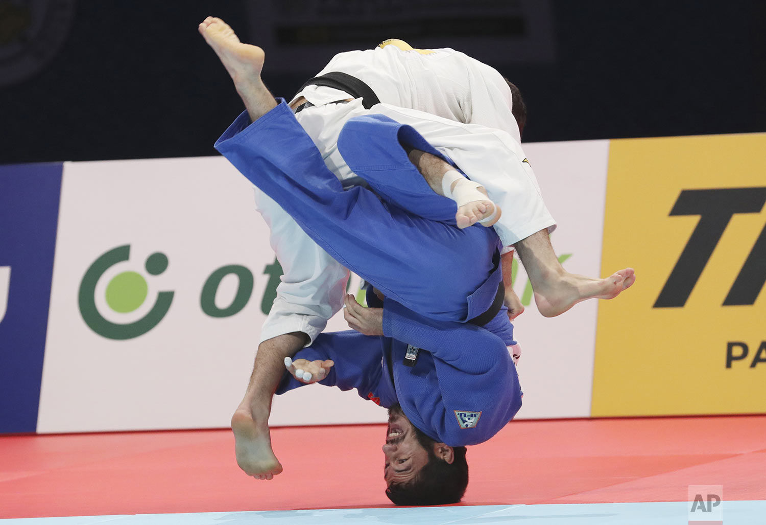 Lukhumi Chkhvimiani, of Georgia, top, competes against Sharafuddin Lutfillaev, of Uzbekistan, during a men's -60 kilogram final of the World Judo Championships in Tokyo, Sunday, Aug. 25, 2019. (AP Photo/Koji Sasahara)