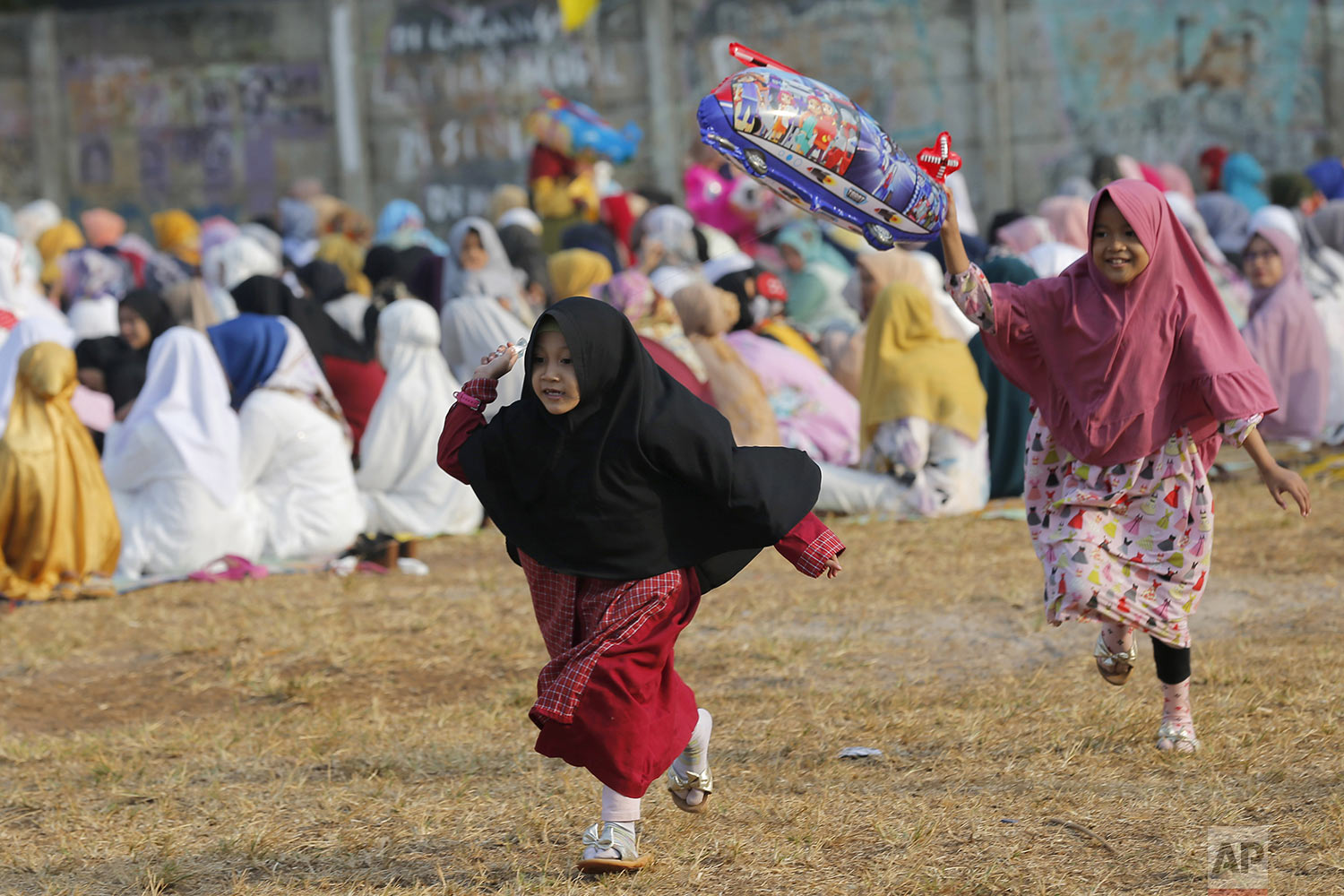 Children play with a balloon after a morning prayer marking Eid al-Adha holidays at a soccer field in South Tangerang, Indonesia, Sunday, Aug. 11, 2019.  (AP Photo/Tatan Syuflana)