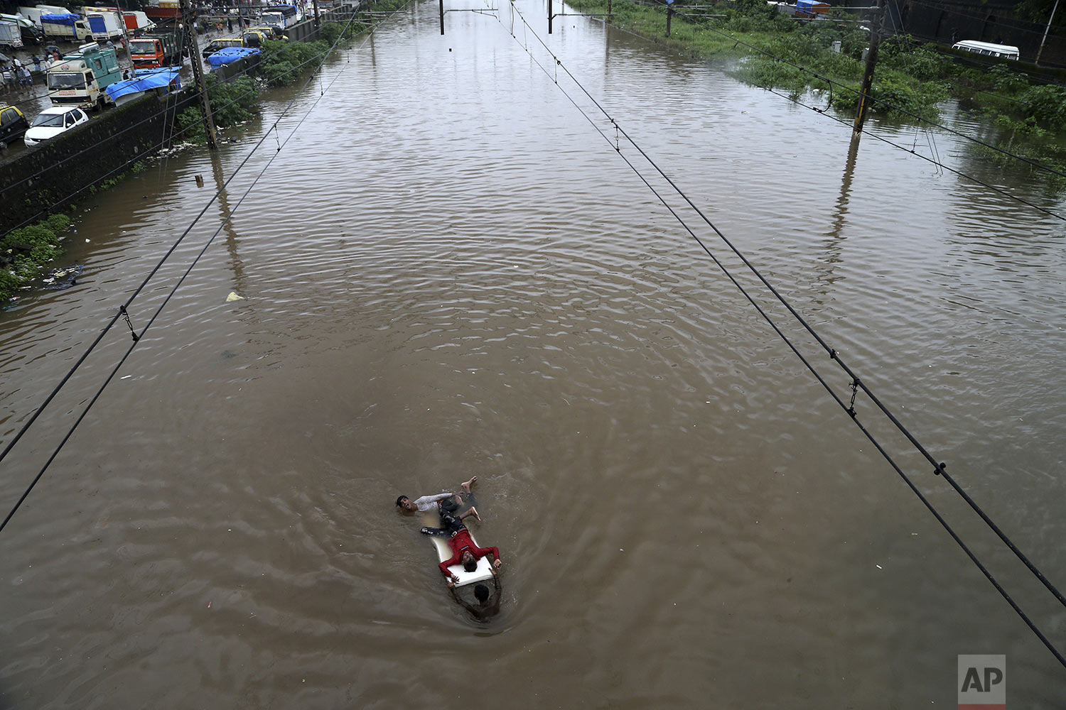 Youth play at a flooded train track following heavy monsoon rains in Mumbai, India, Sunday, Aug. 4, 2019. (AP Photo/Rajanish Kakade)