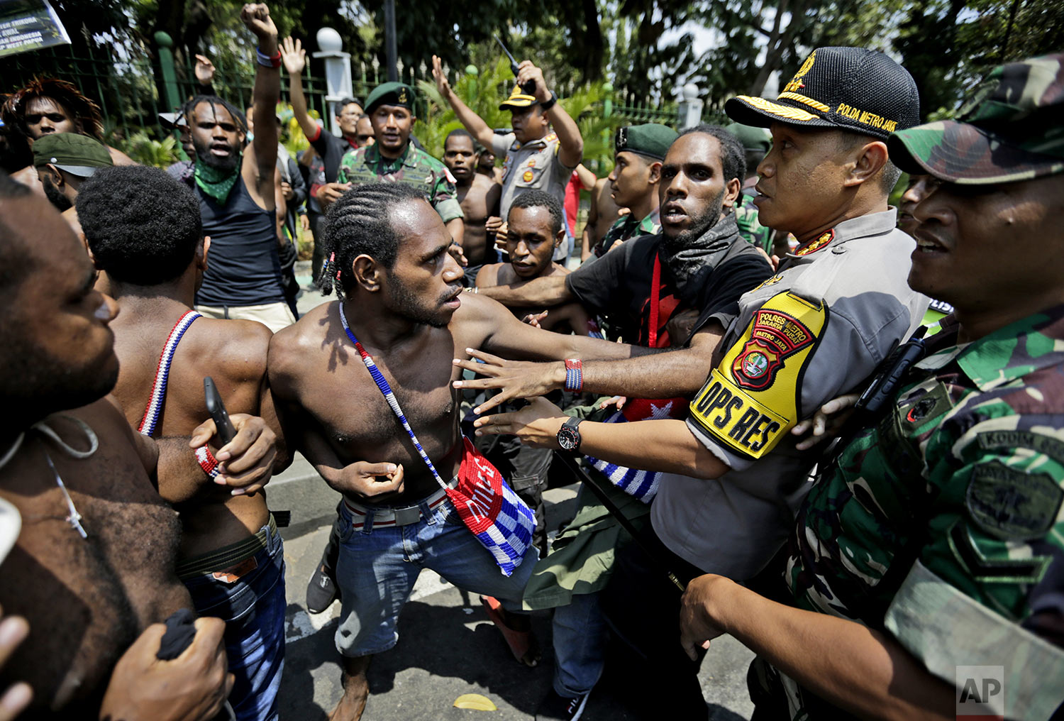 Papuan activists scuffle with police and soldiers during a rally near the presidential palace in Jakarta, Indonesia, Thursday, Aug. 22, 2019. (AP Photo/Dita Alangkara)