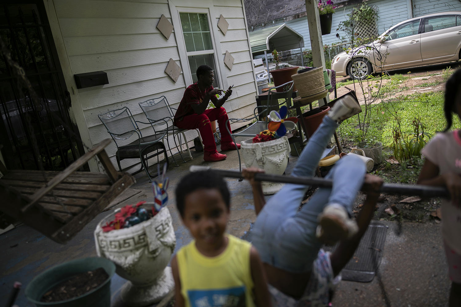 Joshua K. Love relaxes with his nieces and nephews on the front porch of his grandmother's home in Greenwood, Miss., Saturday, June 8, 2019. (AP Photo/Wong Maye-E)