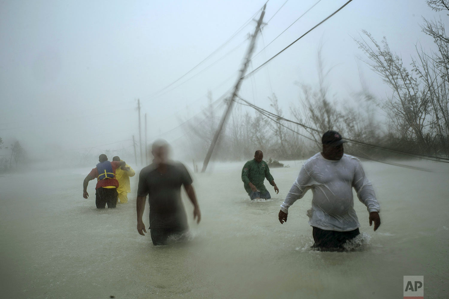 Volunteers wade through a flooded road against wind and rain caused by Hurricane Dorian to rescue families near the Causarina bridge in Freeport, Grand Bahama, Bahamas, Tuesday, Sept. 3, 2019. The storm's punishing winds and muddy brown floodwaters devastated thousands of homes, crippled hospitals and trapped people in attics. (AP Photo/Ramon Espinosa)