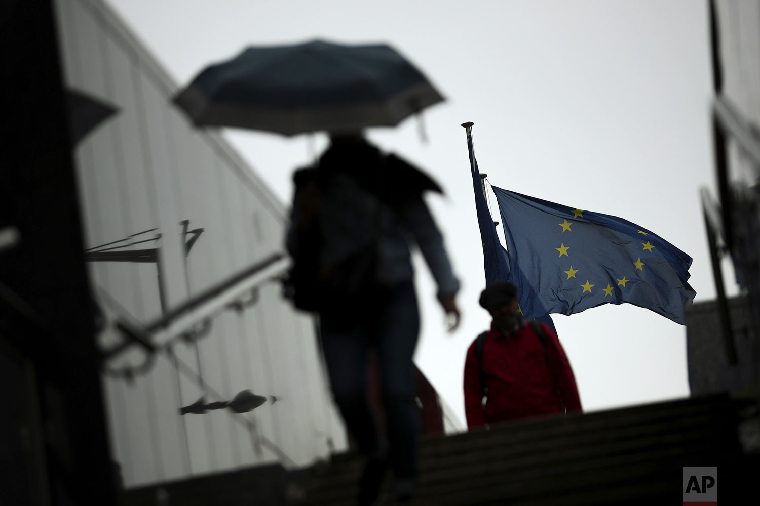 Passers-by shelter against the rain outside the EU headquarters in Brussels, Wednesday, Sept. 4, 2019. The European Union says so far it has received no proposals from the British government aimed at overcoming the impasse in Brexit talks. (AP Photo/Francisco Seco)